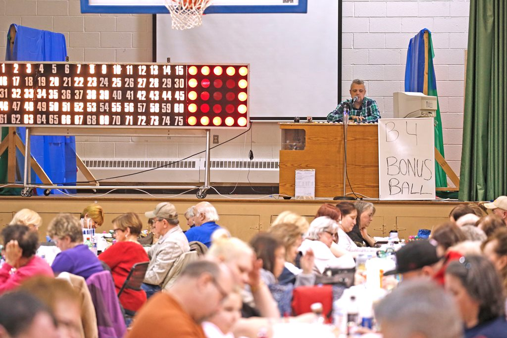 Paul Podsiadlo, on stage, calls bingo at Fourteen Holy Helpers Church in West Seneca, which uses the proceeds to subsidize the cost of sending its children to another Catholic school now that its school has closed.  (Robert Kirkham/Buffalo News)