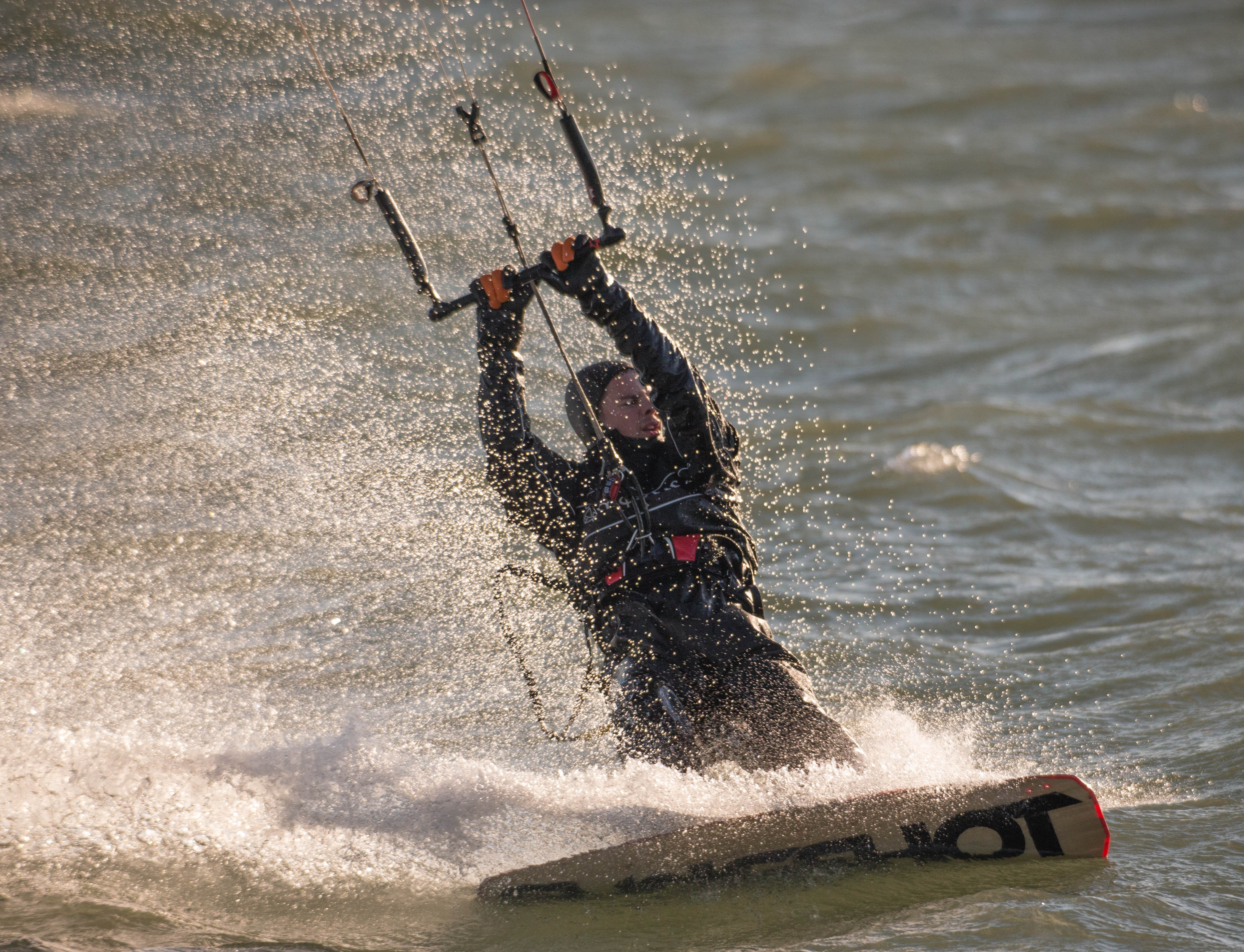 Ryan McGraw of Amherst takes advantage of abnormally warm temperatures and high wind to do some kite surfing in the Outer Harbor, Saturday, Feb. 18, 2017.  (Derek Gee/Buffalo News)