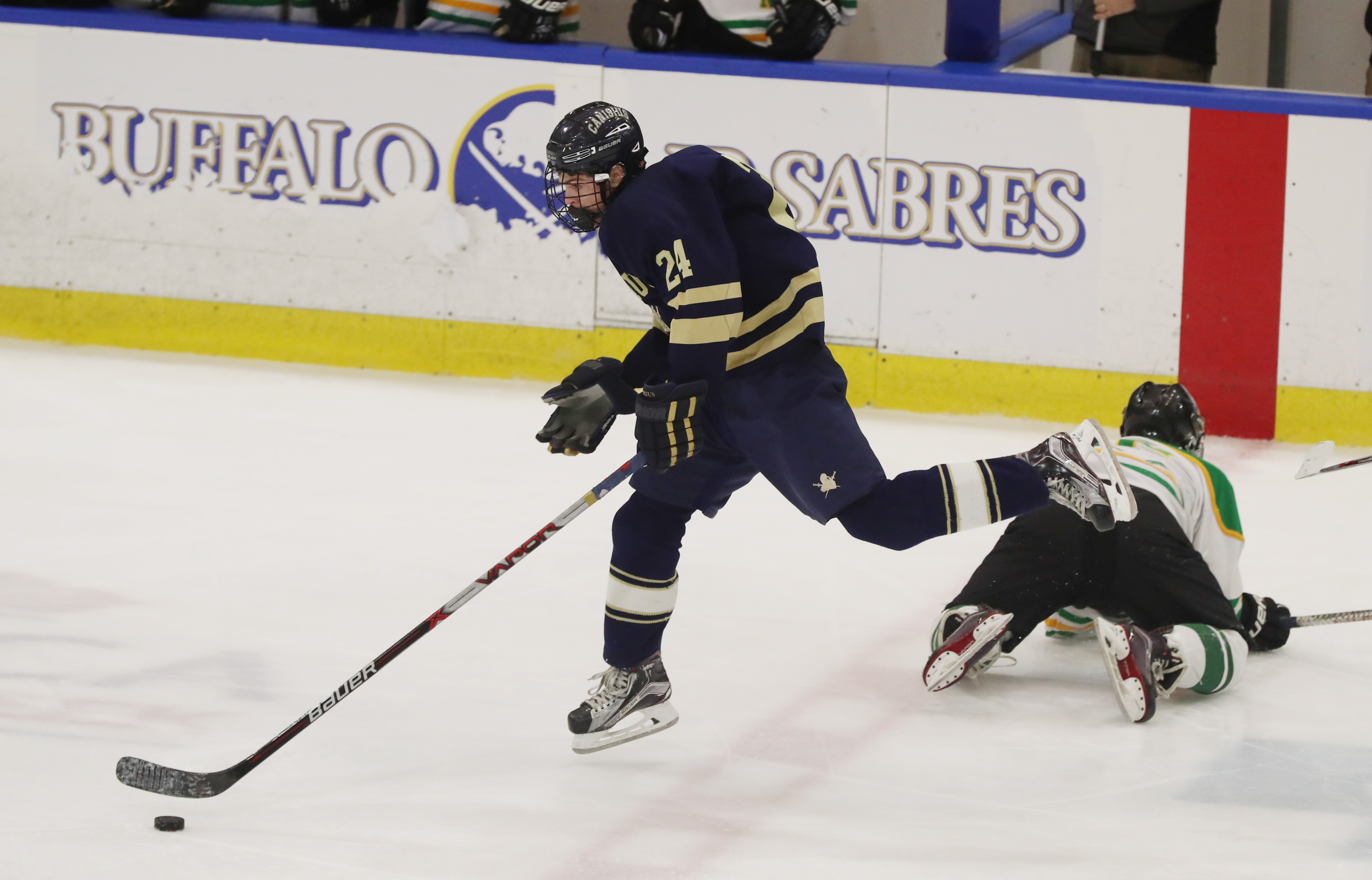 Canisius' Jordan Martin jumps over Bishop Timon-St. Jude's Mike Neenen for the puck in the second period at HarborCenter   (James P. McCoy/Buffalo News)