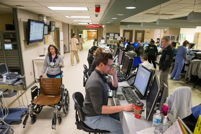 Staff crowds around the central workspace at the heart of the Emergency Department at ECMC.  (Derek Gee/Buffalo News)