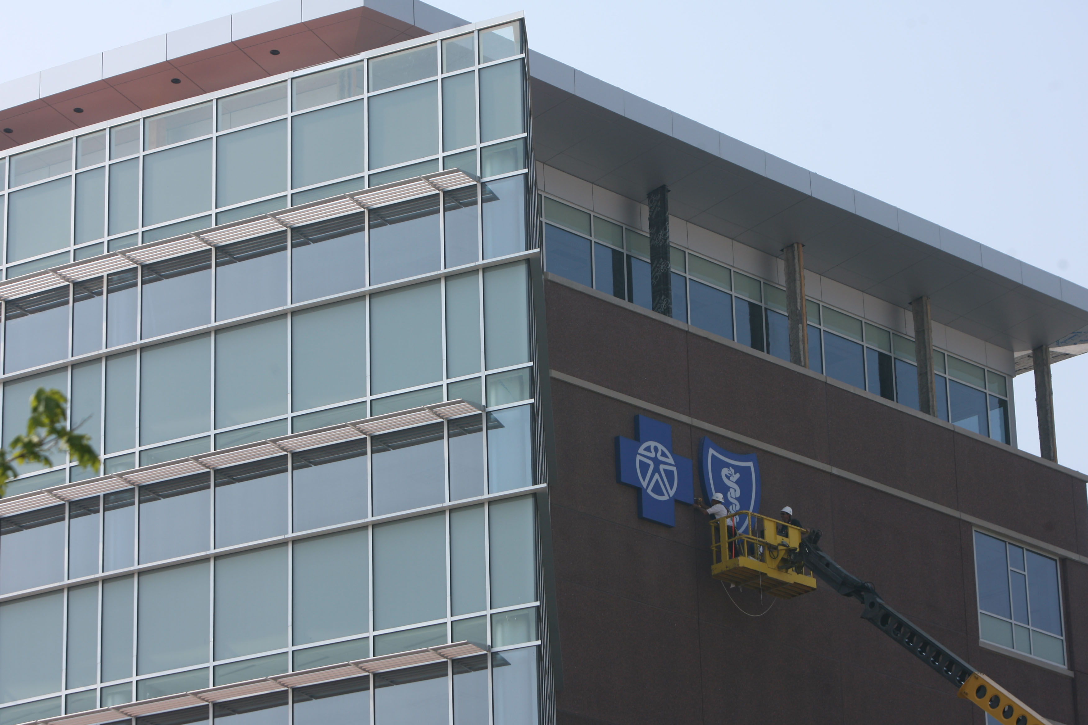 Workers install the BlueCross BlueShield logo on the outside of the company's building in Buffalo in 2007. (Buffalo News file photo)