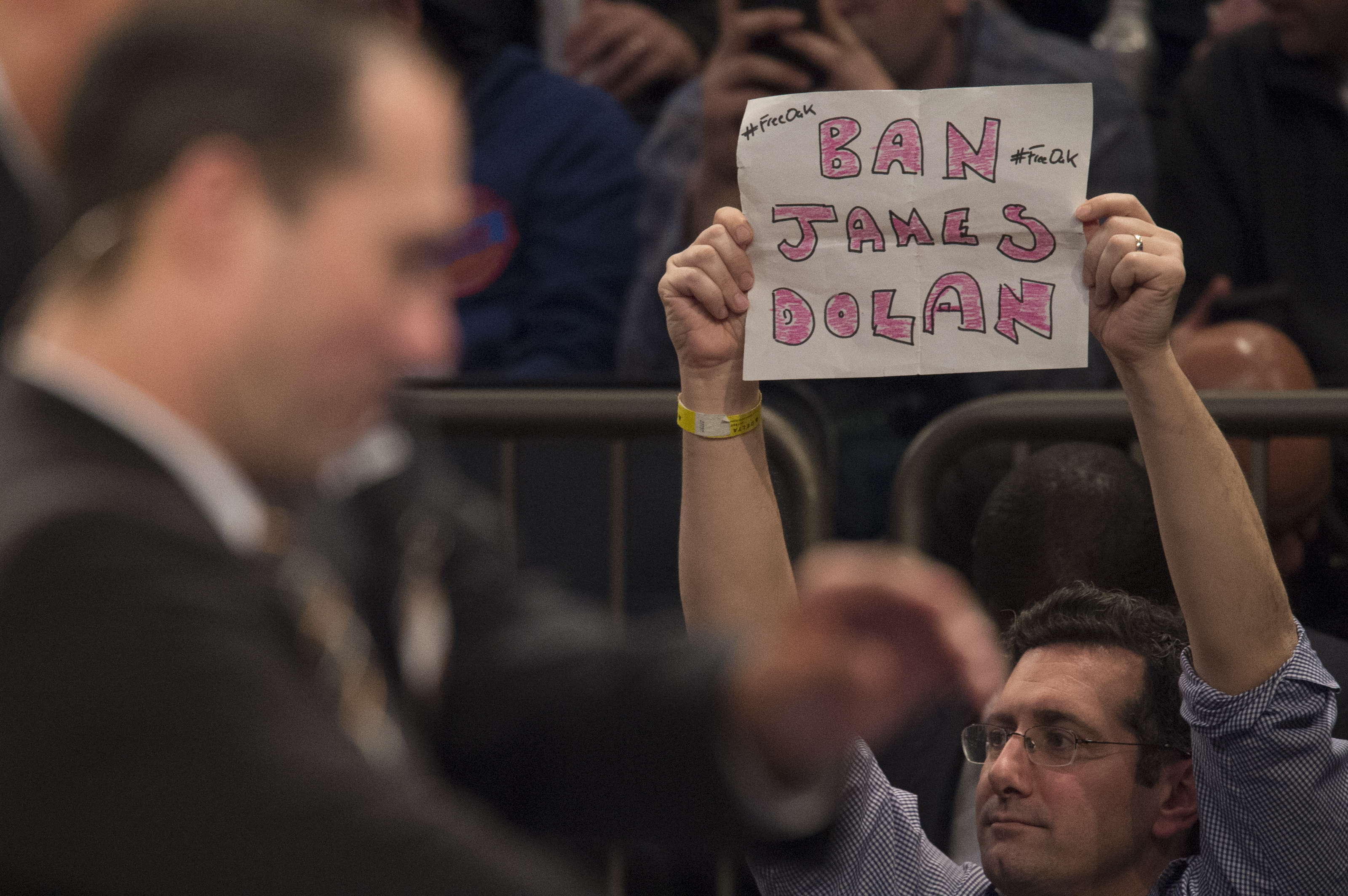 A fan expresses his displeasure with James Dolan at Friday's game Friday hours after the Knicks' owner banned Charles Oakley from Madison Square Garden. (New York Times)