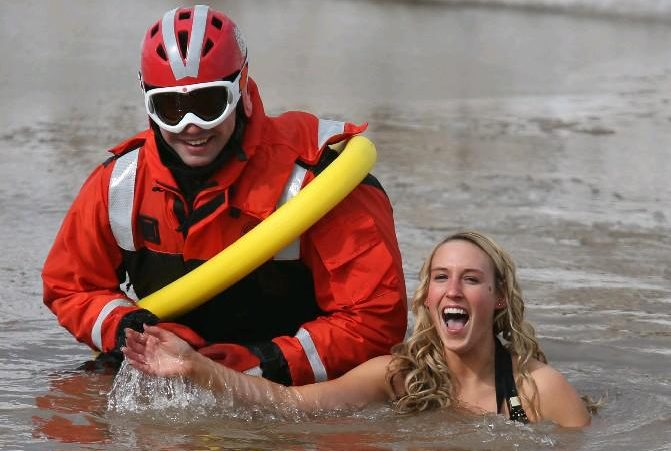 A member of the United States Coast Guard is part of an outer perimeter as Mindy Kramp of Newfane frolics in the cold water of Lake Ontario during the Olcott Lions Club Swim for Sight in 2014. (Buffalo News file photo)