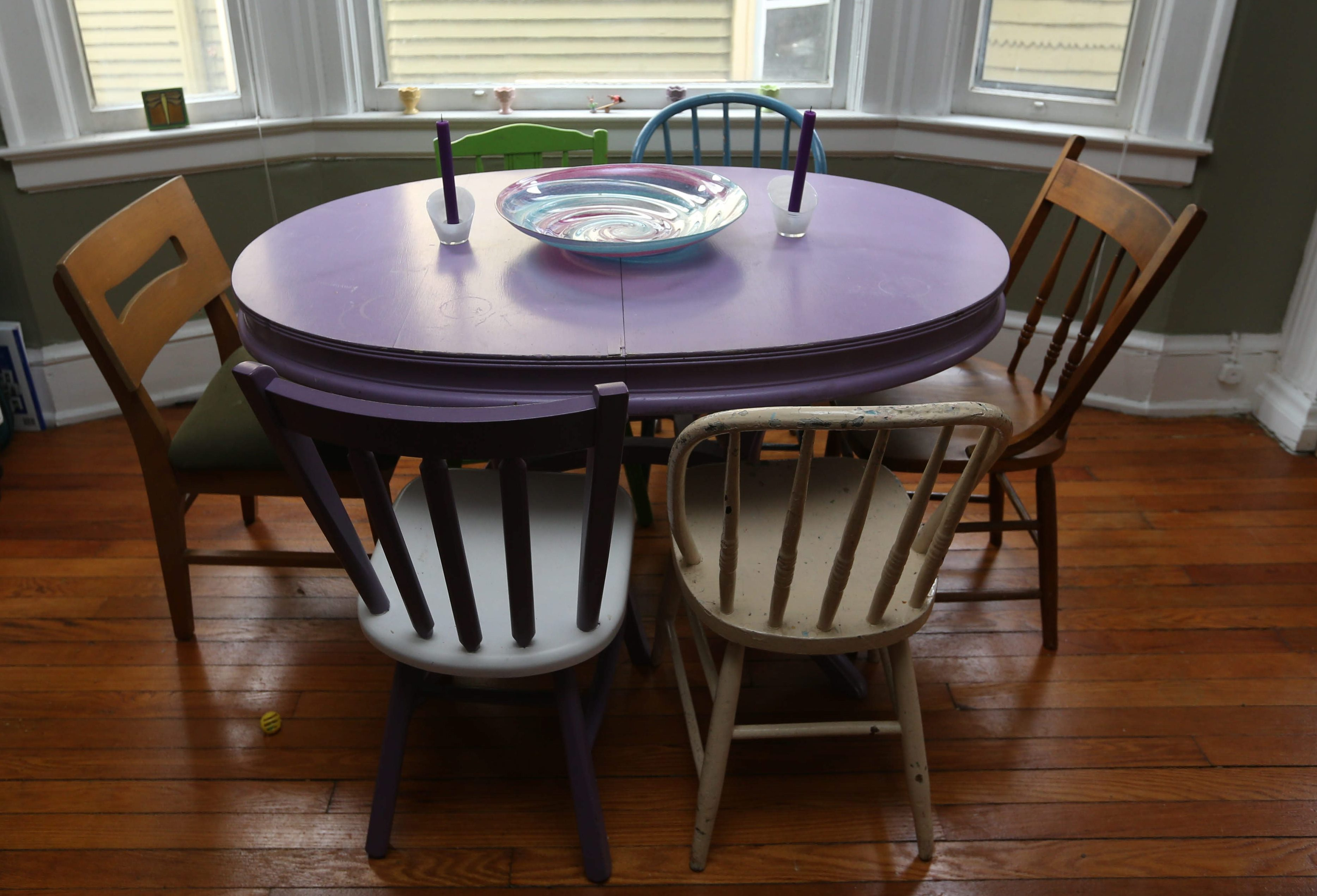 Elmwood Village resident Therese Deutschlander painted the dining chairs in her apartment purple, turquoise and green, while leaving the other three in their original finish. Her place was featured as The Buffalo News 'Home of the Month' in April 2016. (Photo by Sharon Cantillon/Buffalo News)