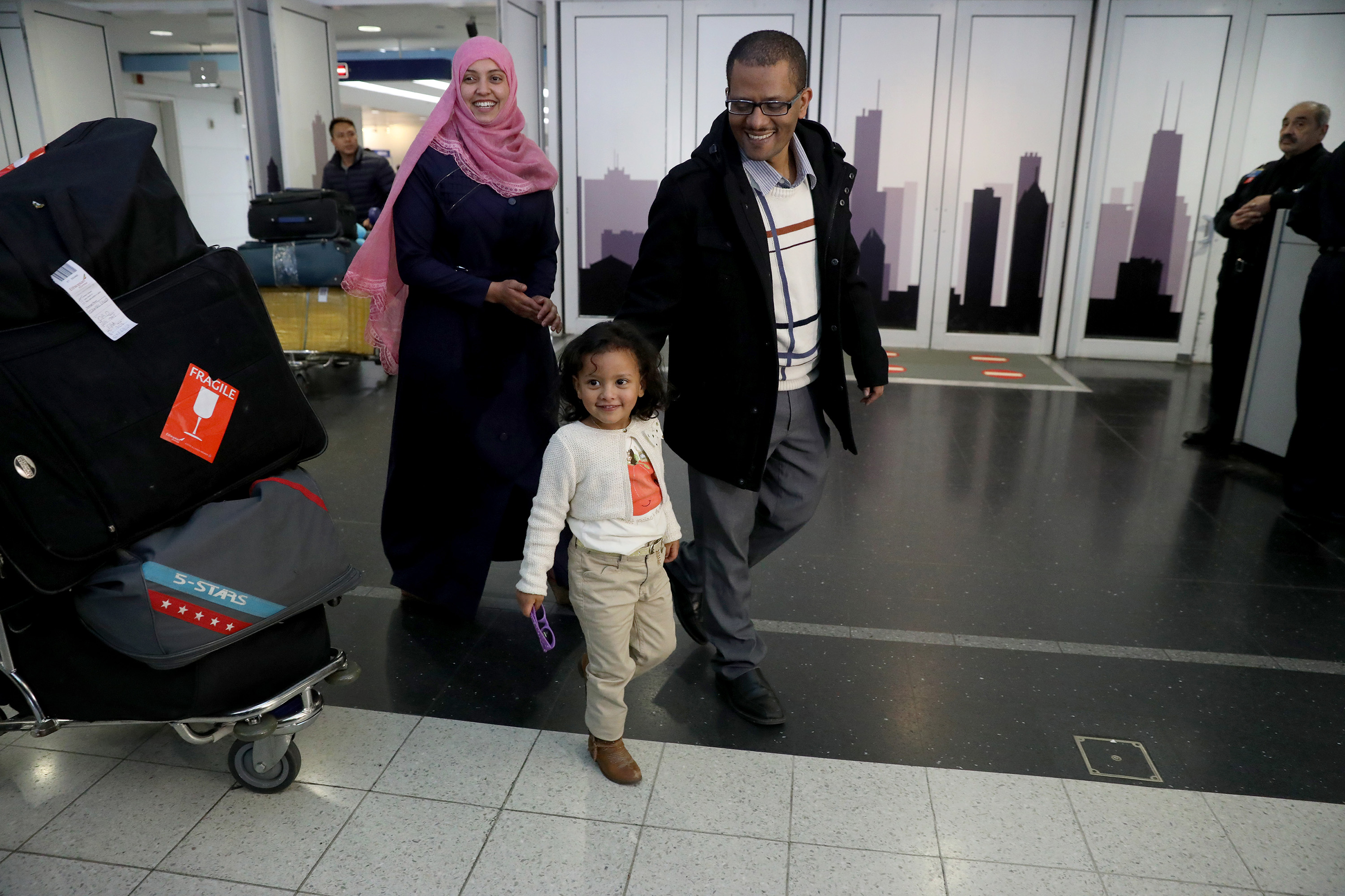 Abdusebur Jemal, right, and Haifa Abdulwahab Hussein Mohammed and their daughter, Rudaynah Jemal, 3, walk through O'Hare International Airport after their reunion on Feb. 5, 2017. (Nancy Stone/Chicago Tribune/TNS)