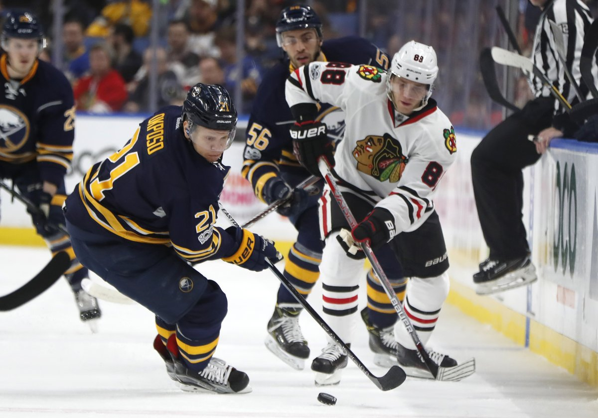 Patrick Kane works the puck against Buffalo's Kyle Okposo (Harry Scull Jr./Buffalo News).