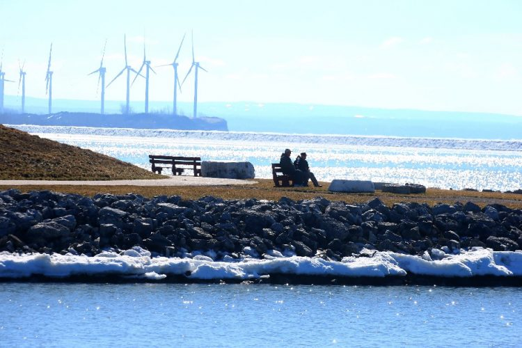 Two people sit and enjoy an unseasonably warm February day from a bench at Wilkerson Point on Buffalo's Outer Harbor. (John Hickey/Buffalo News)