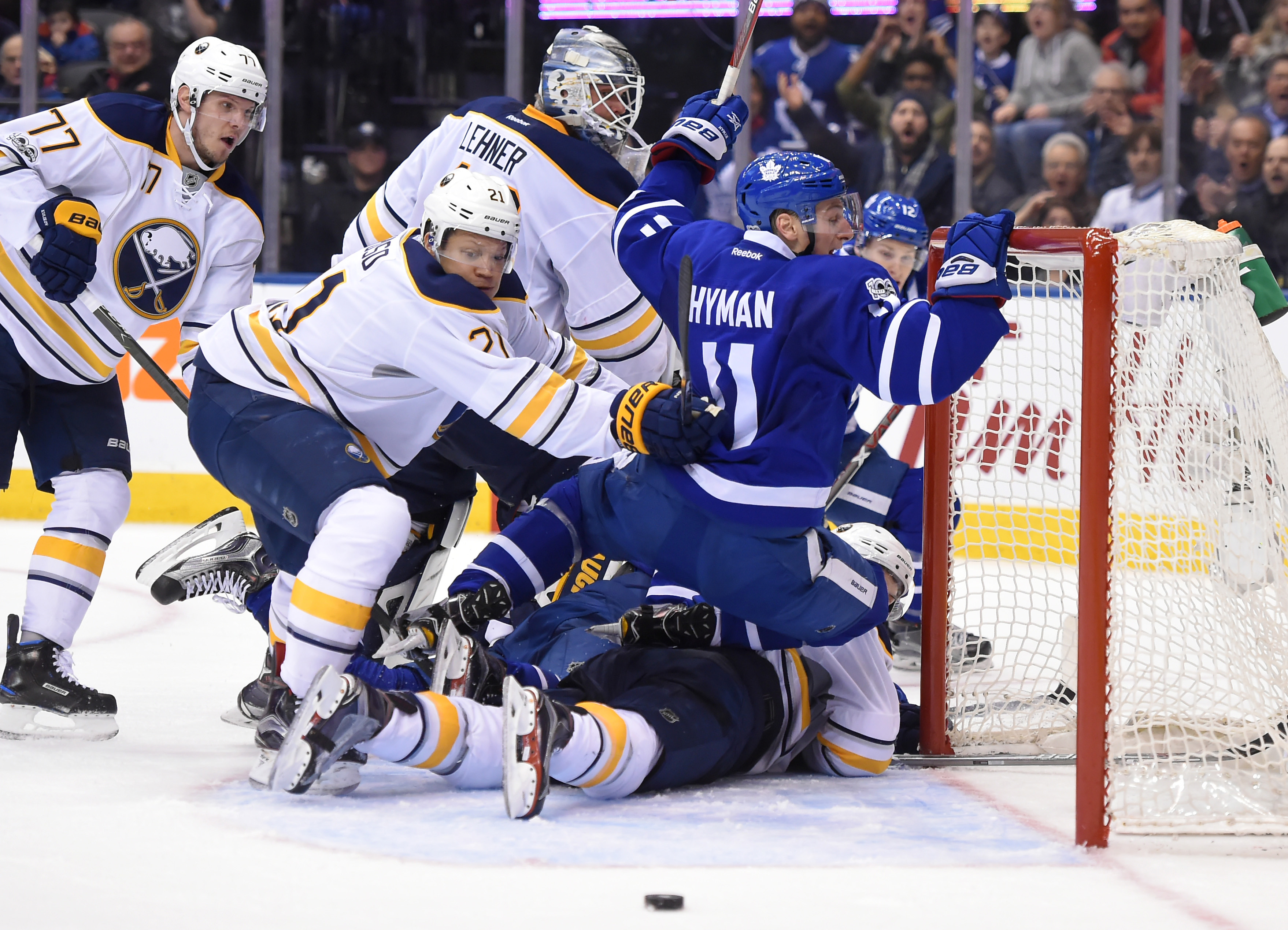 Sabres' Kyle Okposo knocks the Maple Leafs' Zach Hyman into the net as they both go after the loose puck in the second period on Saturday. (USA TODAY Sports)