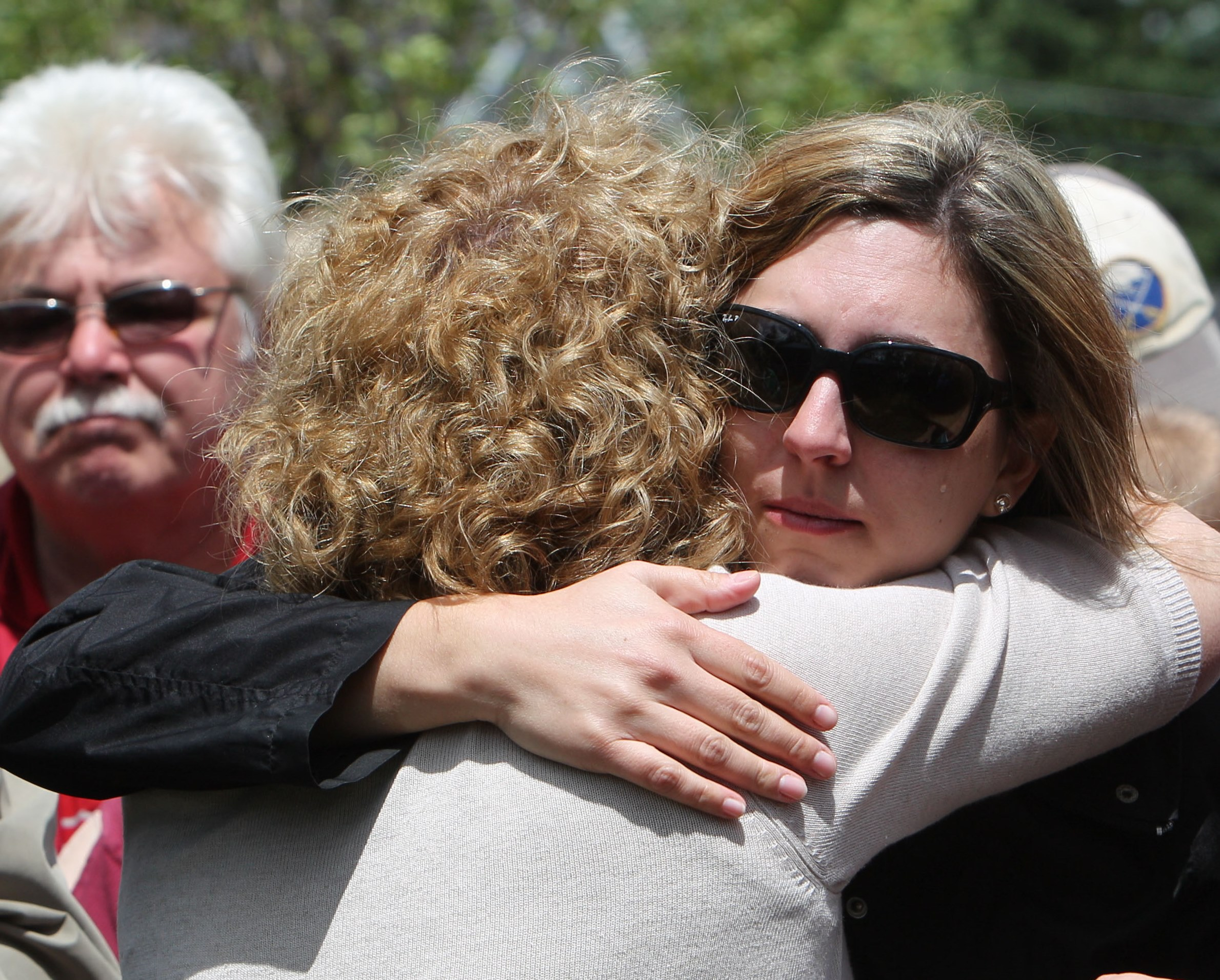 Karen Wielinski, left, hugs her daughter Lori Tiede at the 2012 dedication of the Flight 3407 memorial where their home used to be. (News file photo)