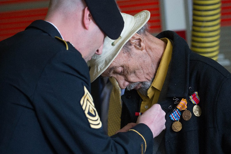 George Watts is presented with the medals he earned in World War II,  but never received, Wednesday by U.S. Army First Sgt. Kyle Davis, left, during a ceremony at the Buffalo Fire Department station on Hertel Avenue .  (Derek Gee/Buffalo News)