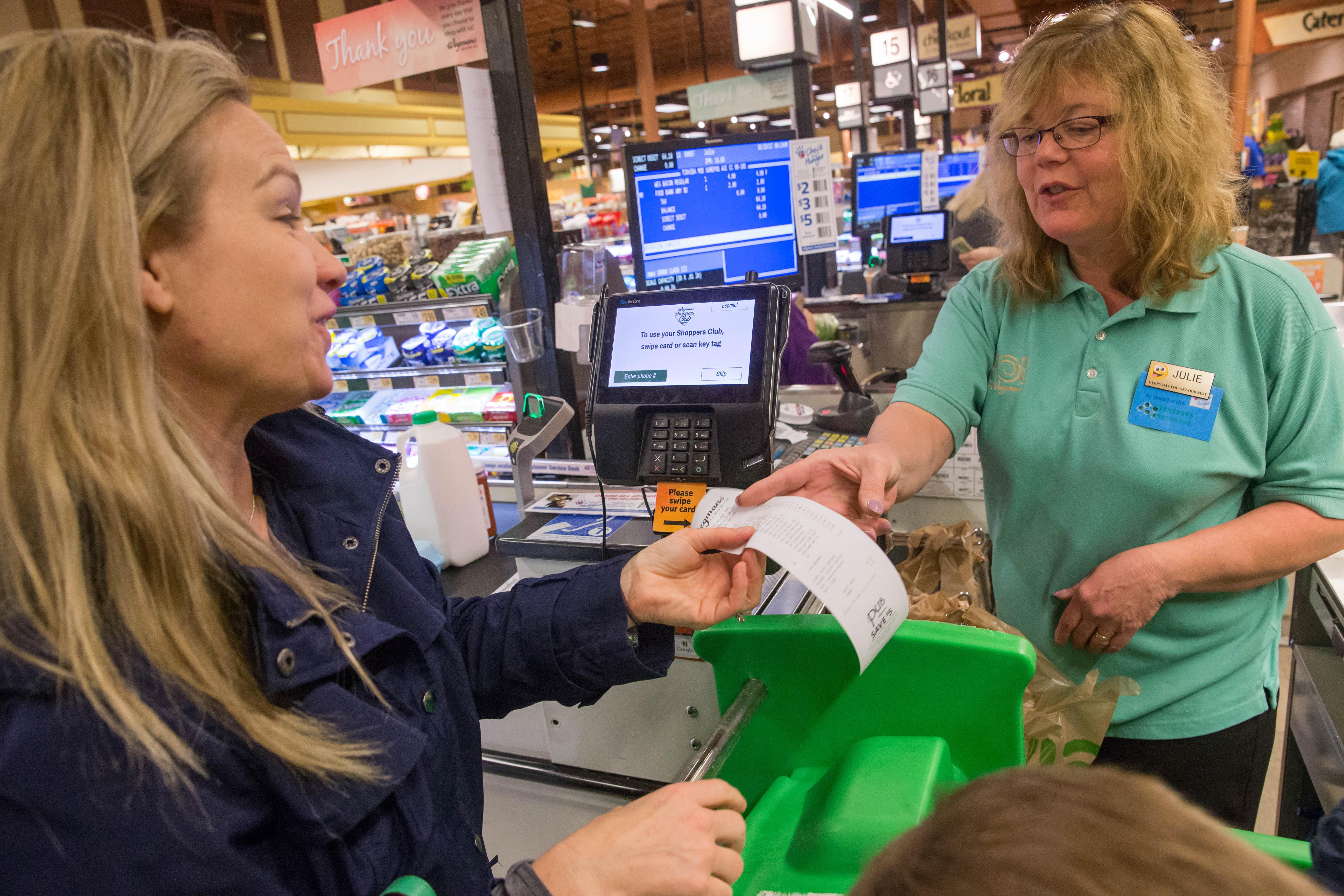 Nora Macnamee of Lewiston gets her receipt from cashier Julie Juzwicki while checking out at the Wegmans in Niagara Falls.  (Derek Gee/Buffalo News)