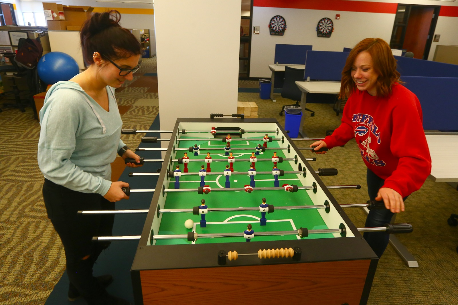 New Era's customer service administrator Sarah Morris, left, and Morgan Kissel, a customer relations analyst, play foosball while at work. (John Hickey/Buffalo News)