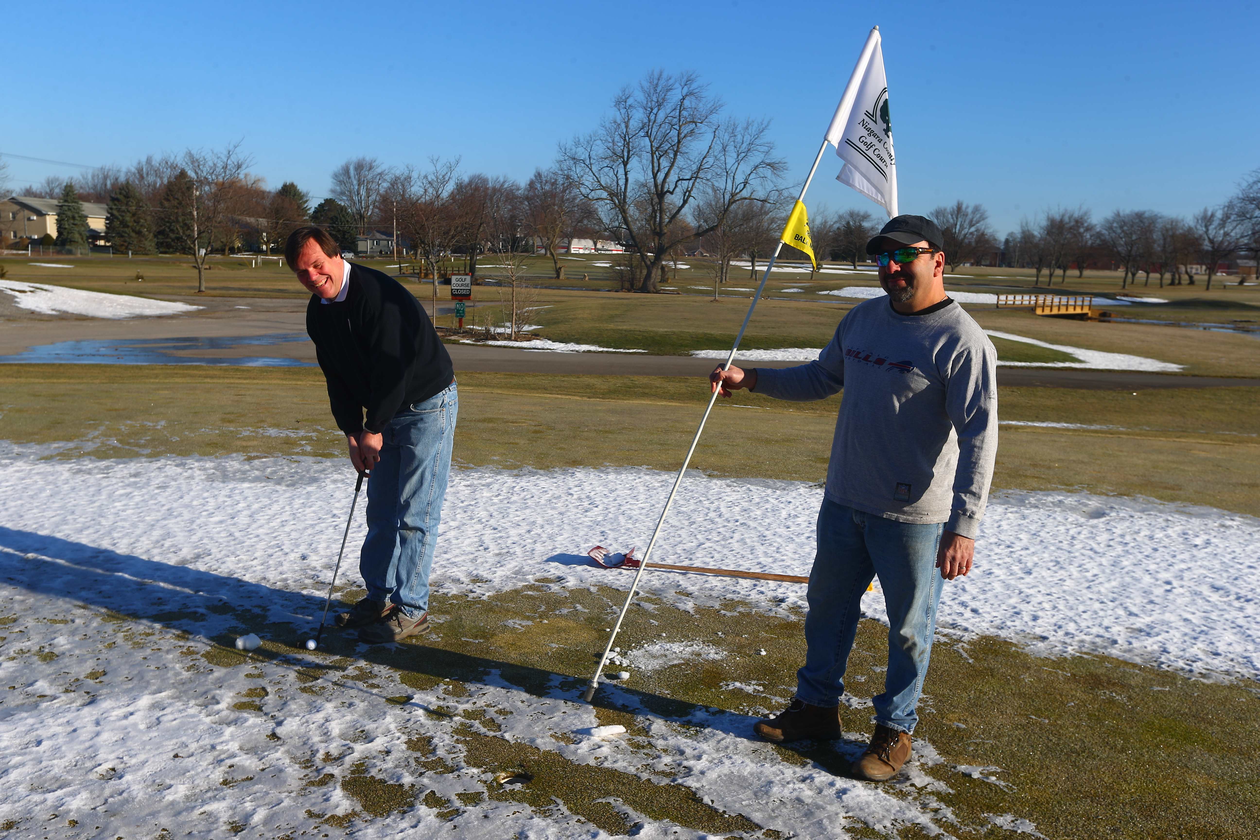 Niagara County Golf Course golf director Thomas Yaeger putts as  Tom Farrell, the course's superintendent greens keeper, provides some assistance with the flag. (John Hickey/Buffalo News)