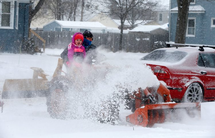 Ian Woodams gets some help clearing his driveway from his daughter Madeline at their home in Kenmore on Tuesday. (Mark Mulville/Buffalo News)