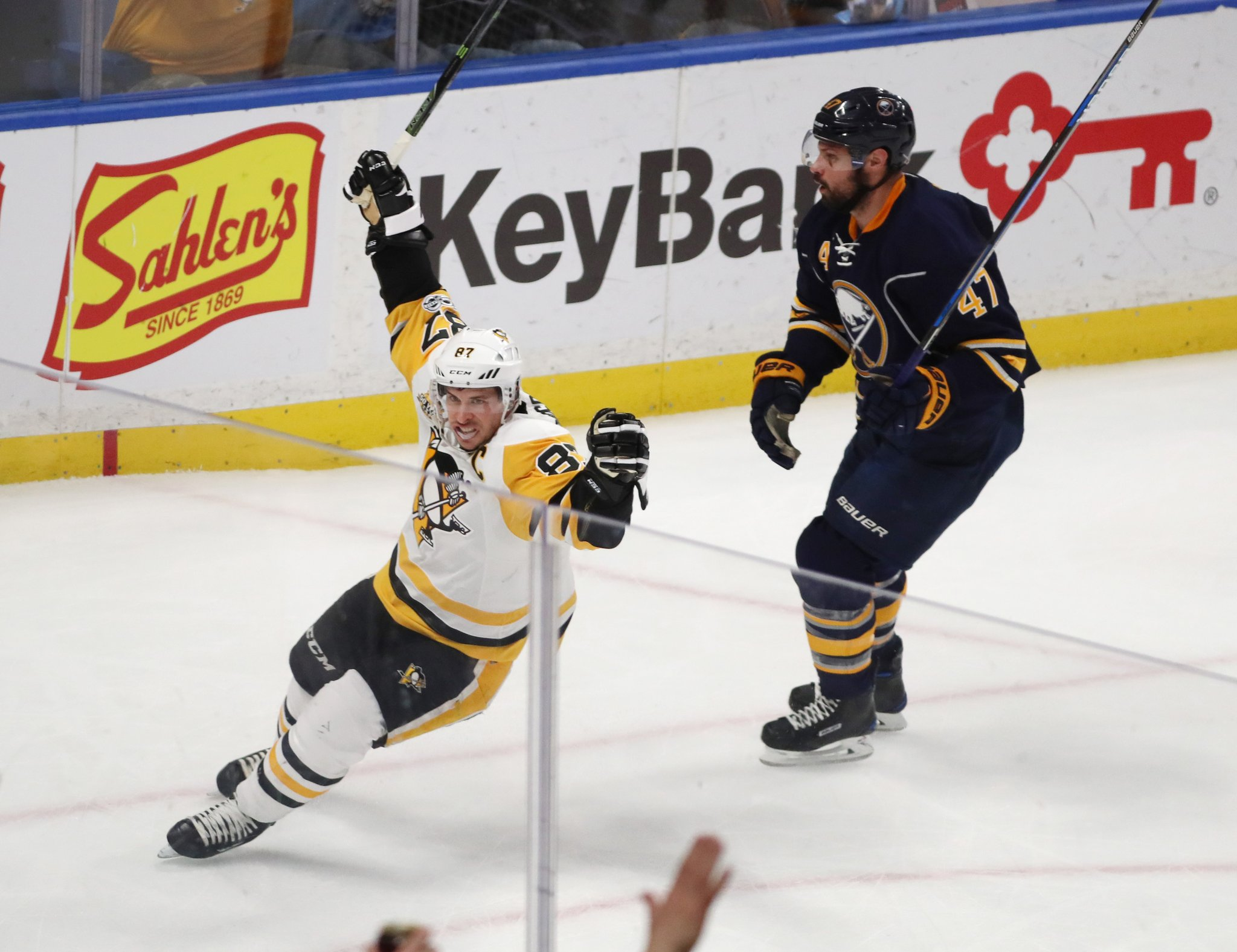 Sidney Crosby celebrates the opening goal after skating past Zach Bogosian and the Sabres. (James P. McCoy/Buffalo News)