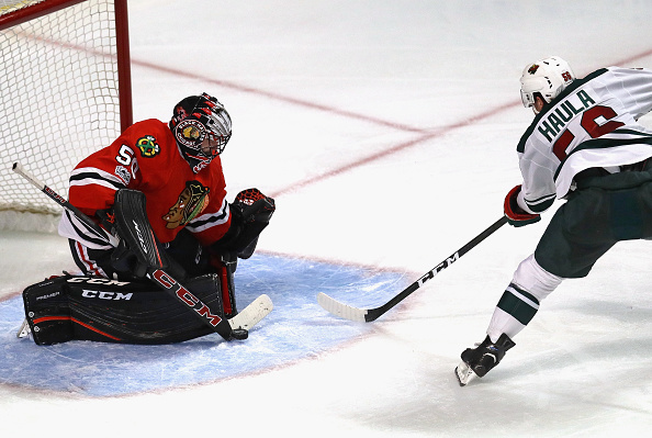 Corey Crawford of the Blackhawks makes a save against Erik Haula of the Wild during Chicago's third straight win over Minnesota Sunday in United Center (Getty Images).