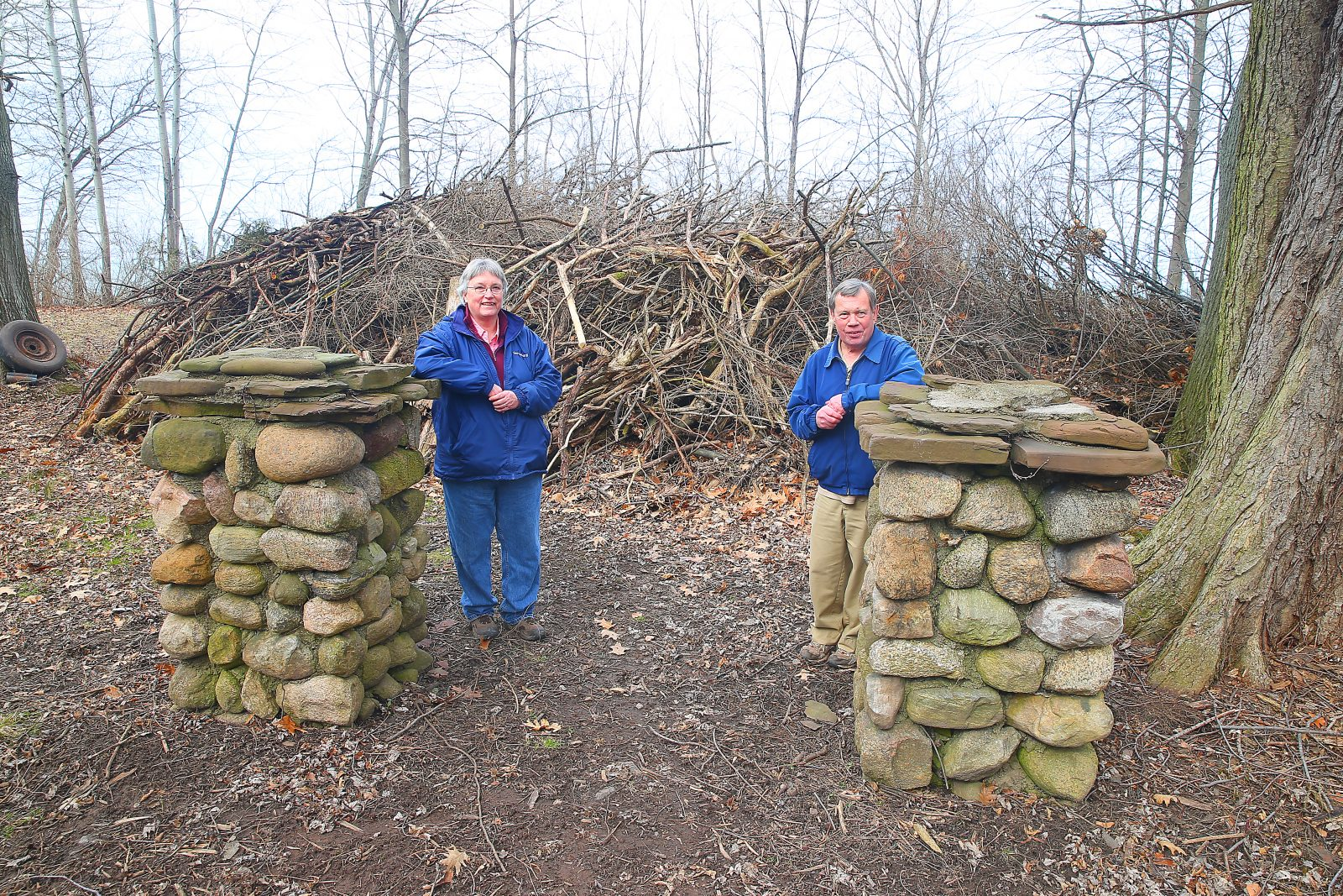 Cheryl and Mike Wertman stand by two stone pillars that were once part of the Drake Estate in Golden Hill State Park. Behind them is one of the many brush piles they have made in the months they have been working at the site, almost daily since last spring. (John Hickey/Buffalo News)