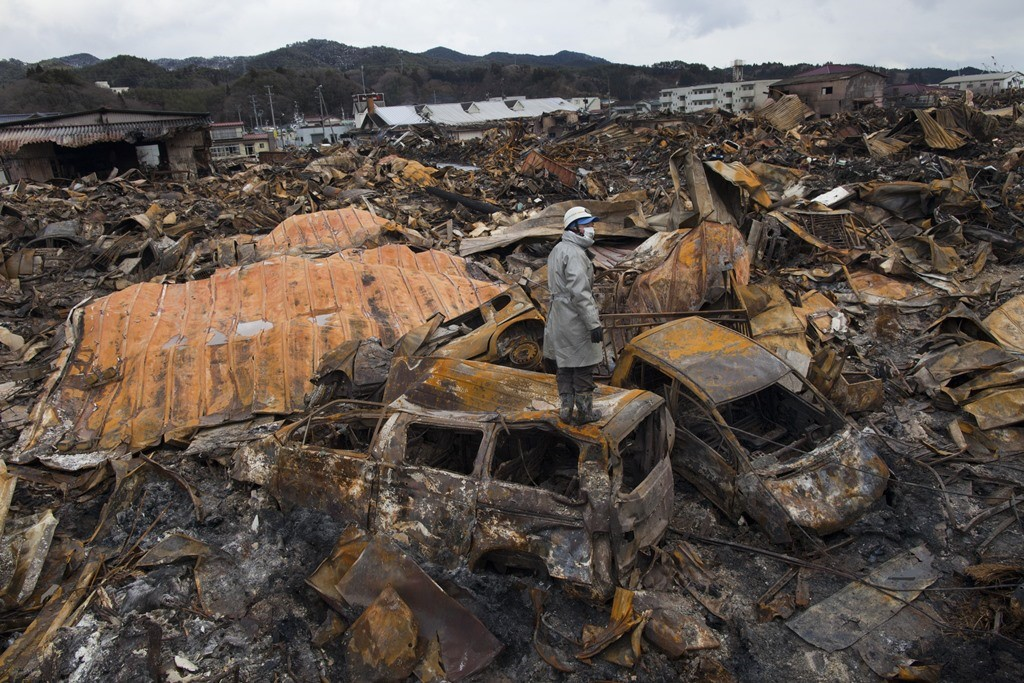 A worker atop a burned vehicle looks for bodies in the rbble of a village leveled by the devastating earthquake and tsunami that struck Japan on March 11, 2011, destroying the Fukushima Dalichi nuclear plant and killing 15, 984. (Getty Images)