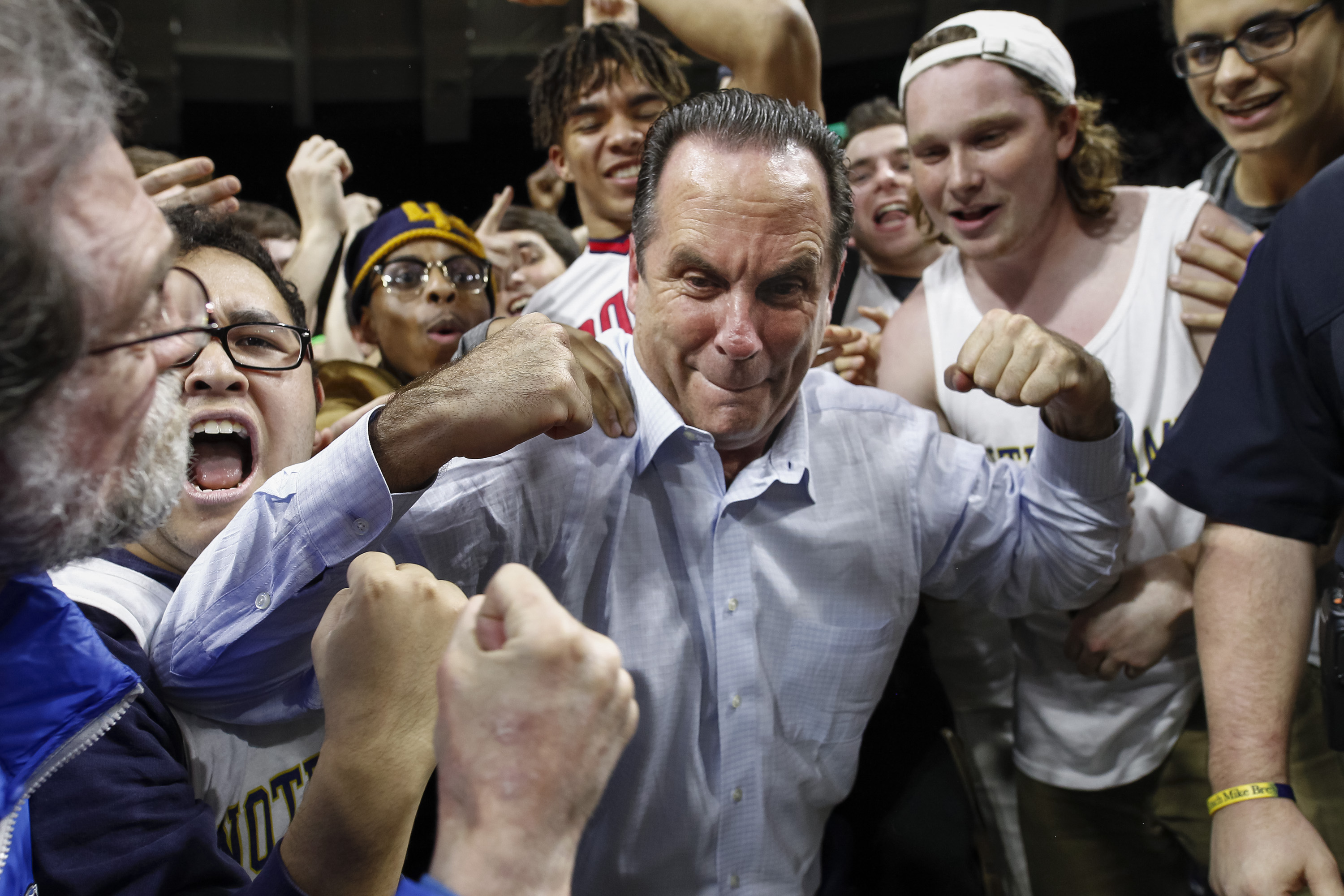 Notre Dame head coach Mike Brey (who has a family sports connection to Buffalo) celebrates with students after beating Florida State this season. (Getty Images)