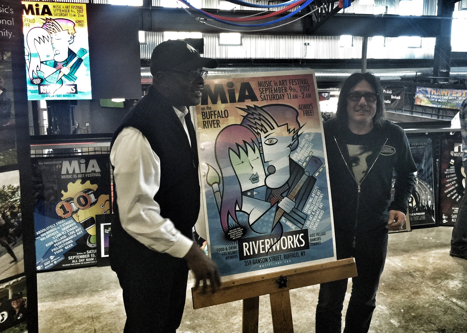 Mayor Byron Brown and Music is Art founder and president Robby Takac pose with a poster announcing the 2017 edition of the Music is Art Festival. (Jeff Miers/buffalo News)