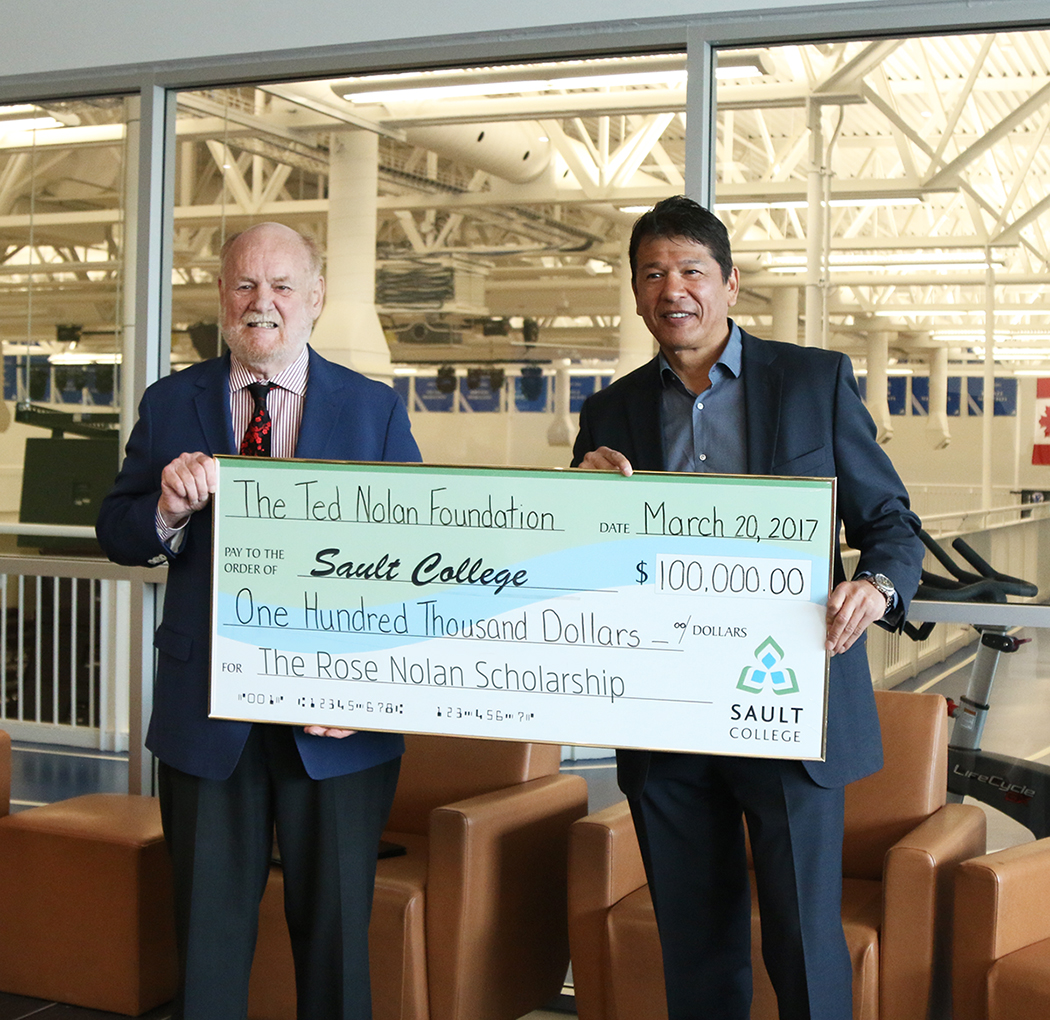The $100,000 donation by Ted Nolan, right, will be divided into two yearly scholarships at Sault College. Dr. Ron Common, school president, accepts the check. (Photo courtesy of Sault College)