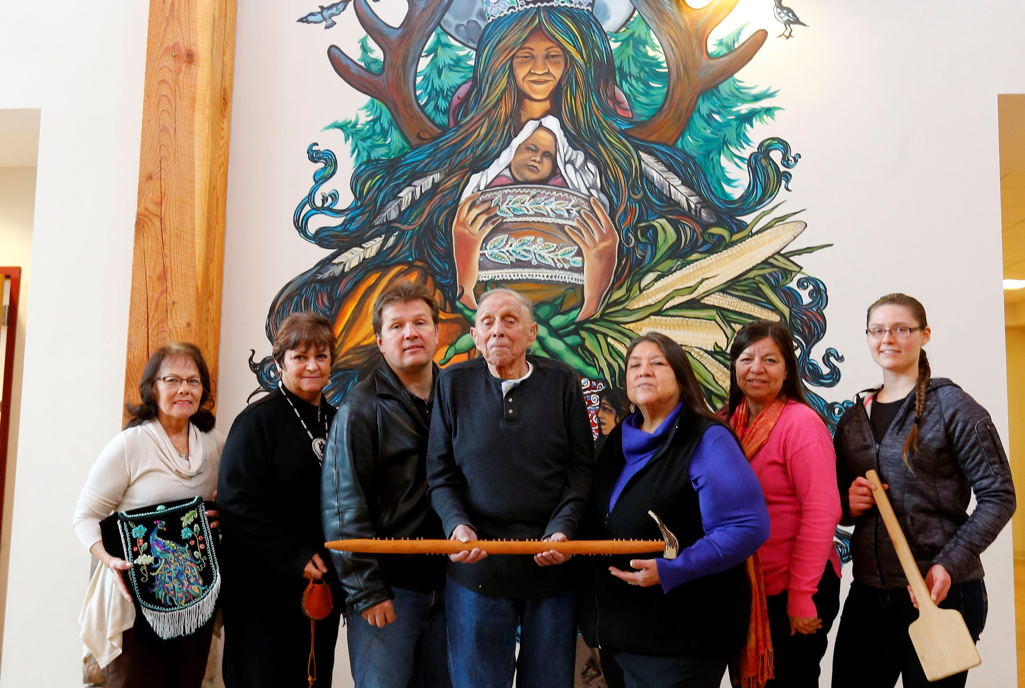 Members of the History Group of the Tuscarora Nation plan an informative open house March 25 at the Nation House. They are, from left, Judy Judware, Yesenaruhcreh Wendy Bissell, Vince Schiffert, Chief Leo Henry, Gagehatdat Schandream, Angela Jonathan, and Taylor Hummel.  They are holding an example of beadwork, a traditional condolence cane related to the naming of a chief, and a wooden paddle used to stir cooking corn bread. (Mark Mulville/Buffalo News)