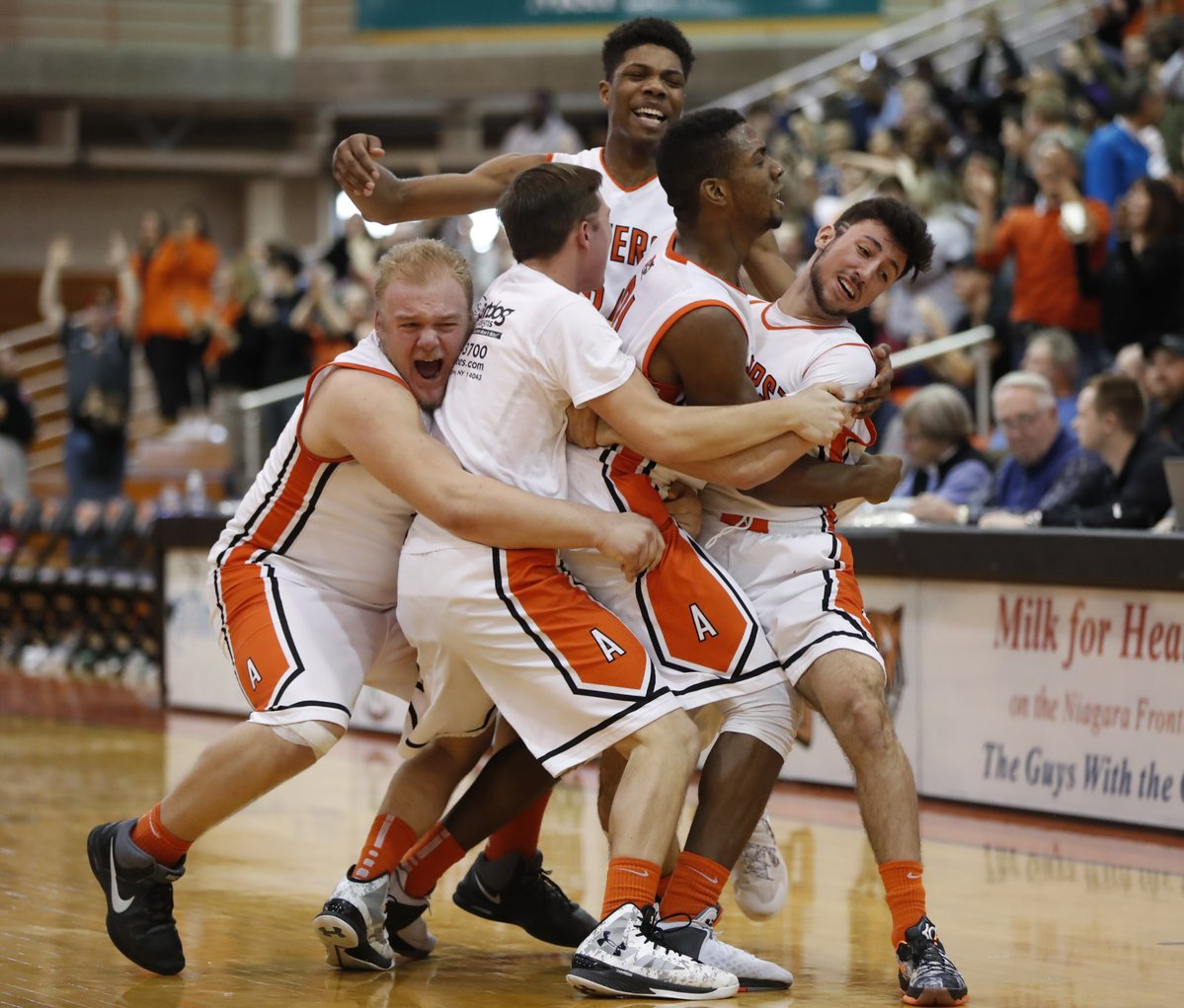 Jordan Barr is mobbed by his Amherst teammates after his putback enabled the Tigers to repeat as Section VI Class A-2 champions. (Harry Scull Jr./Buffalo News)