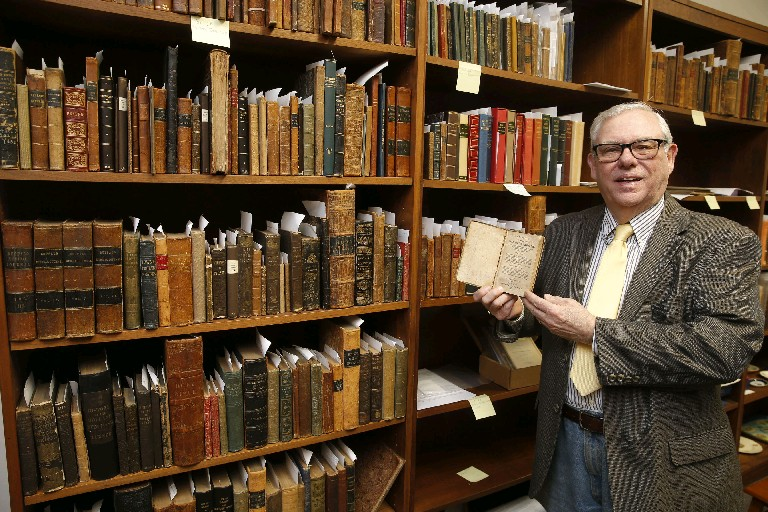 "Ronald Cozzi shows a first edition of ""The Narrative of the Life of Mary Jamison"" from the early 1800s that is in the collection at his Old Editions Book Shop in Buffalo. (Robert Kirkham/Buffalo News)"
