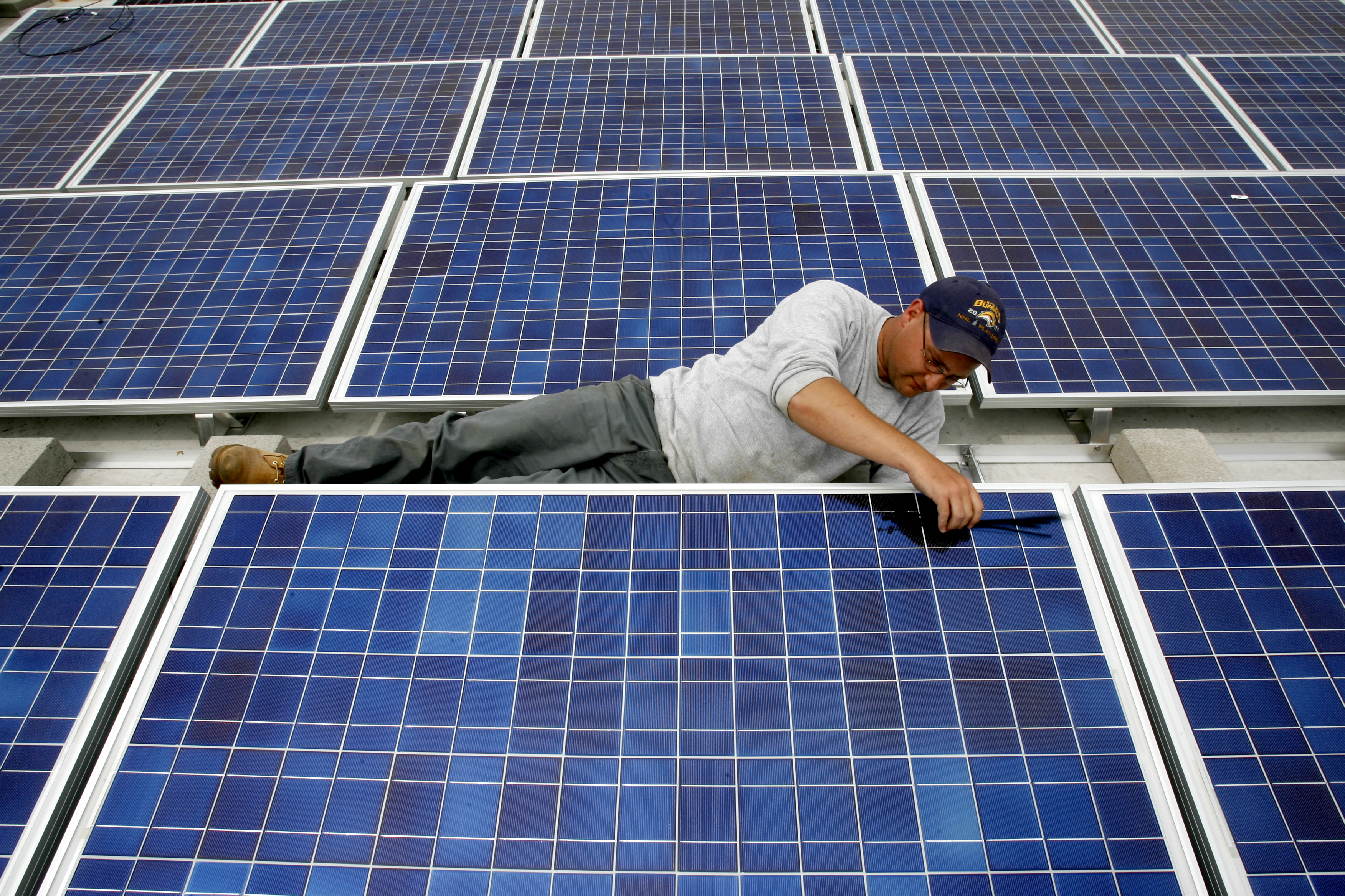 A solar panel technician with Solar Liberty installs solar modules on a roof. (Buffalo News/ Robert Kirkham file photo)