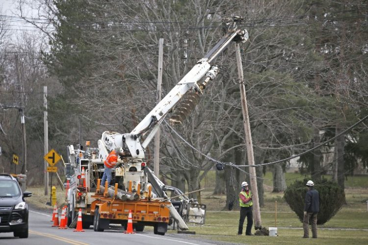 Crews continued to restore power to areas knocked out by Wednesday's wind storm. More than 70,000 customers remained without power across Western New York as of about 3 p.m. Thursday.  (Robert Kirkham/Buffalo News)