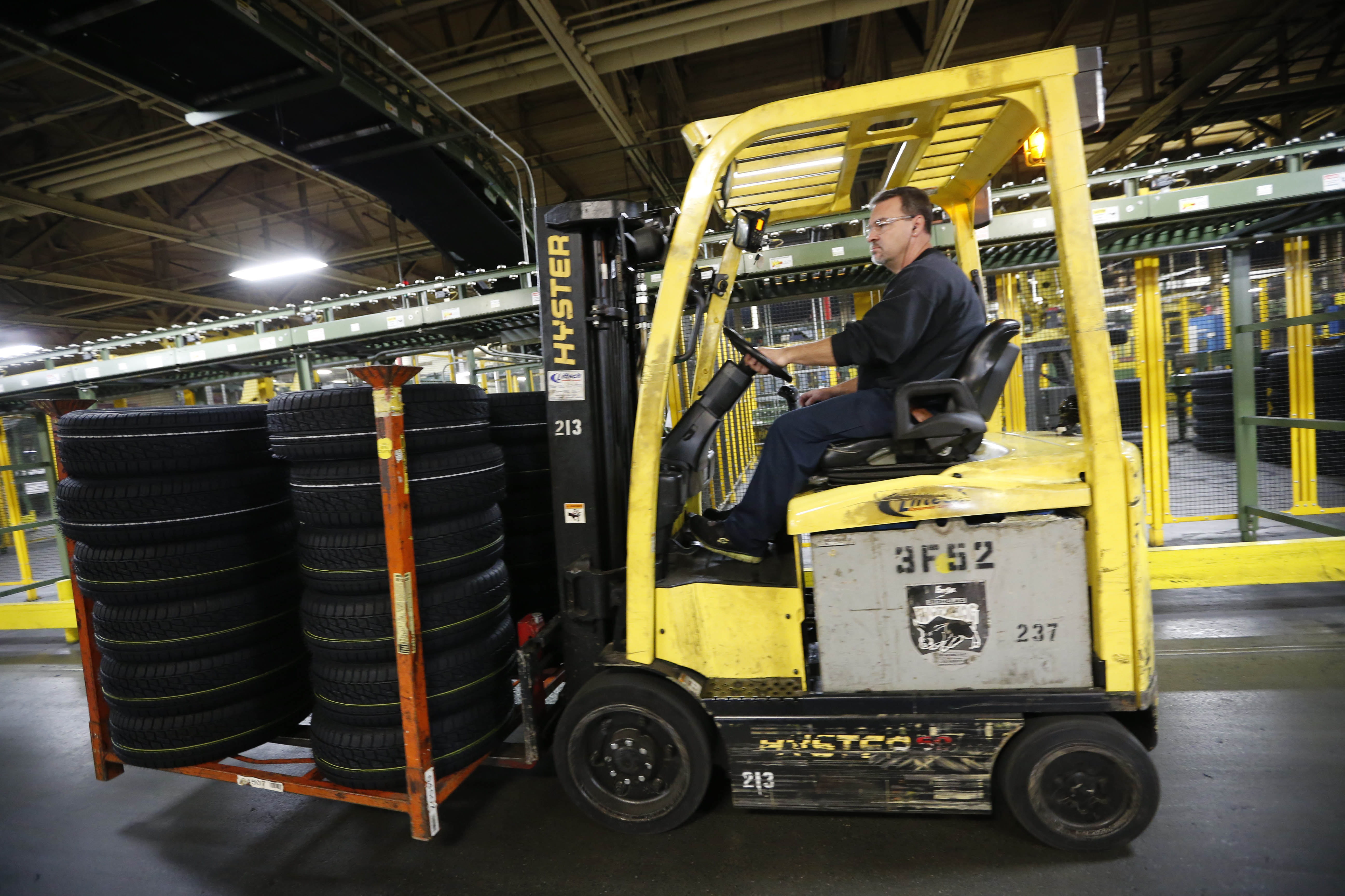 A worker carries a load of new tires at the Sumitomo Rubber USA tire manufacturing plant in Tonawanda in November.  (Derek Gee/Buffalo News file photo)