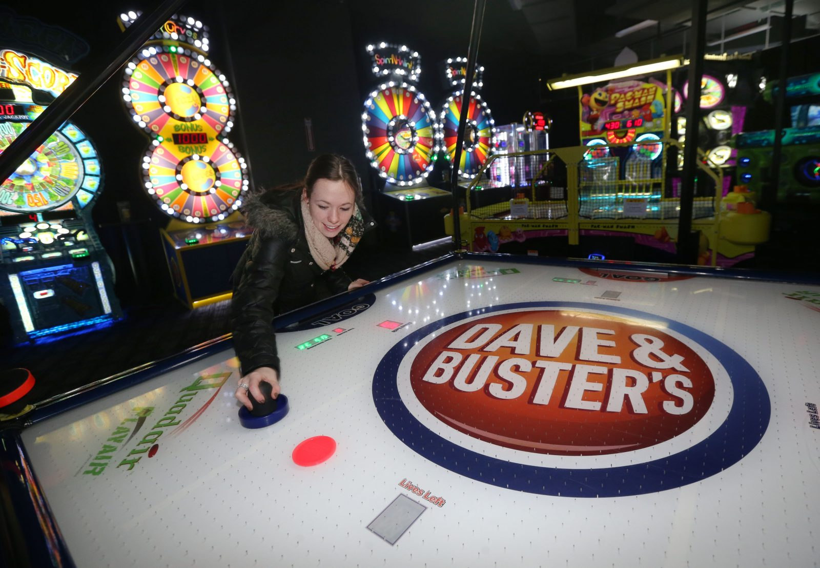 Jacklyn Kertzie plays air hockey, one of the many games at Dave & Buster's in Walden Galleria. (Sharon Cantillon/Buffalo News)