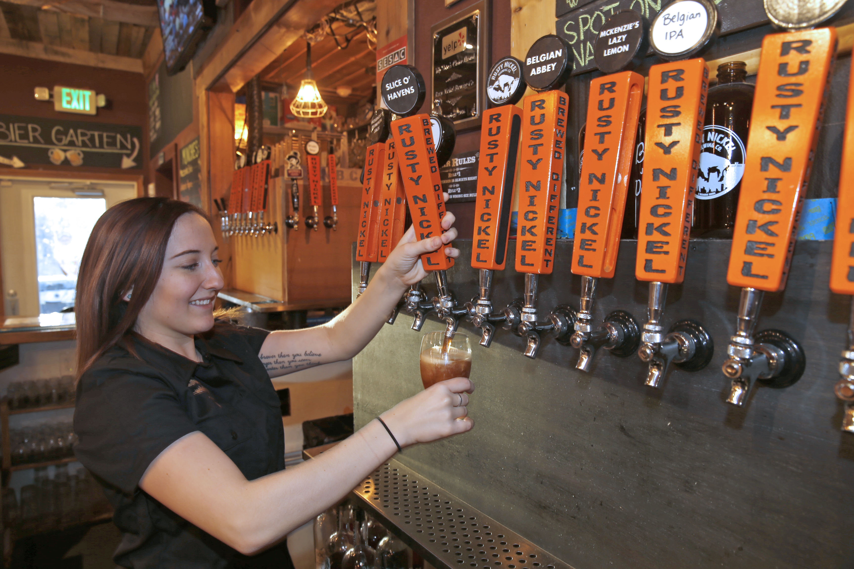Margaret Cavese pours a glass of the hearty Slice of Havens at the Rusty Nickel Brewing Co.  (Robert Kirkham/Buffalo News)