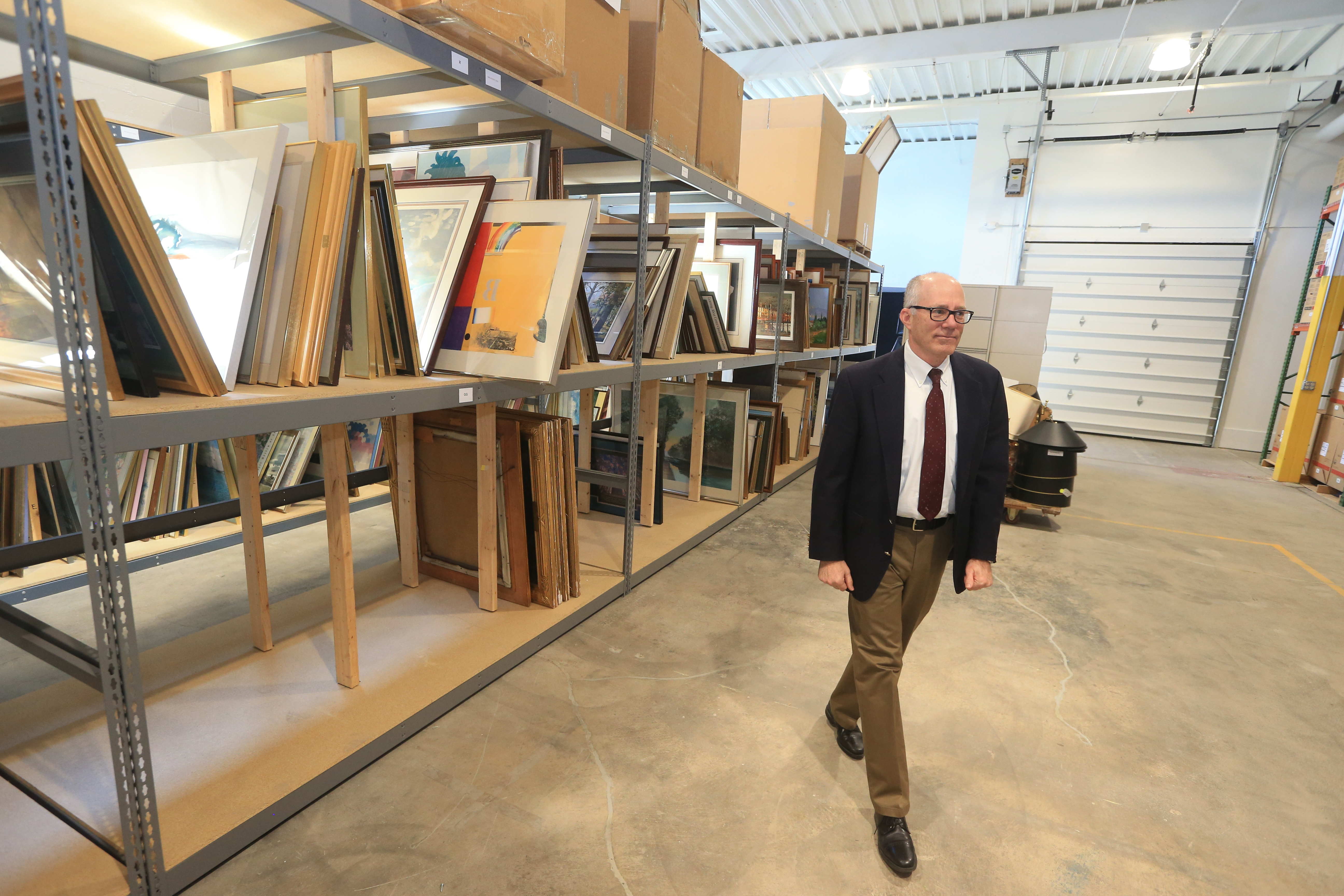 Keith Belanger, M&T senior vice president of corporate services, looks at warehoused paintings and prints for sale at the  M&T Corporate ReUse store. (John Hickey/Buffalo News)