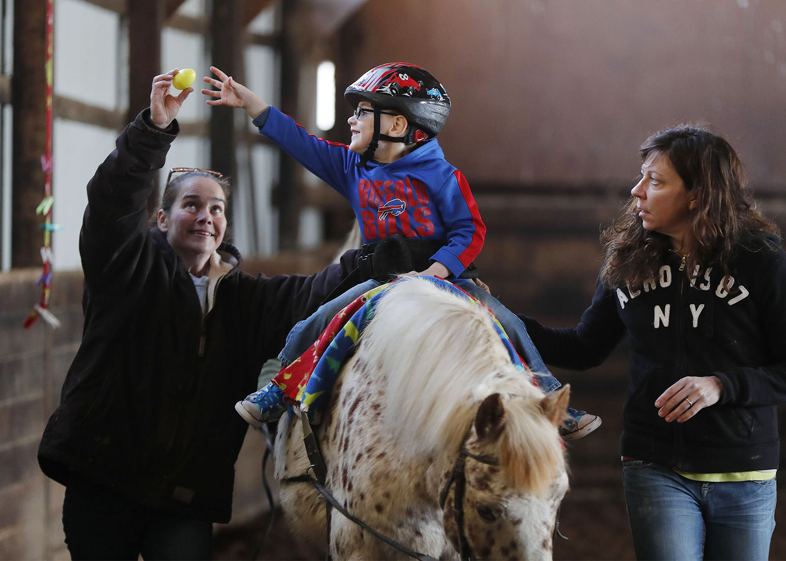 Jackson Buyea, 4, of Lancaster, does his hippotherapy session with therapists Patti McGrane, left, and Carol Heuser. Balancing on the horse helps Jackson develop core strength and teach him how to shift his weight. (Mark Mulville/Buffalo News)
