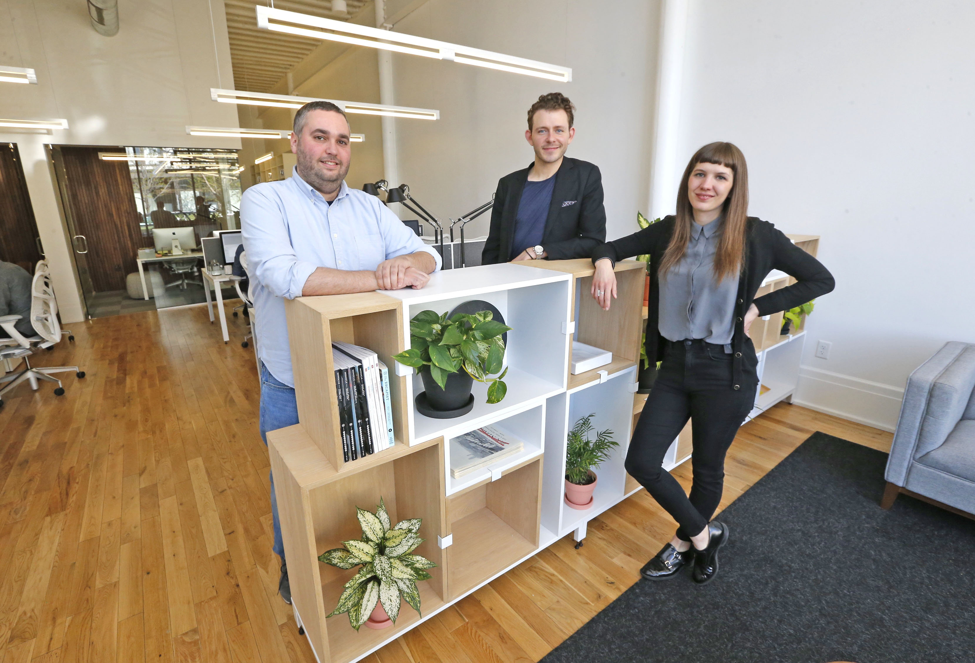Block Club Content Strategist Ben Siegel, left, along with Brandon Davis, founder and creative director, and Julie Molloy, designer, at their office on Main Street in Buffalo.  (Robert Kirkham/Buffalo News)