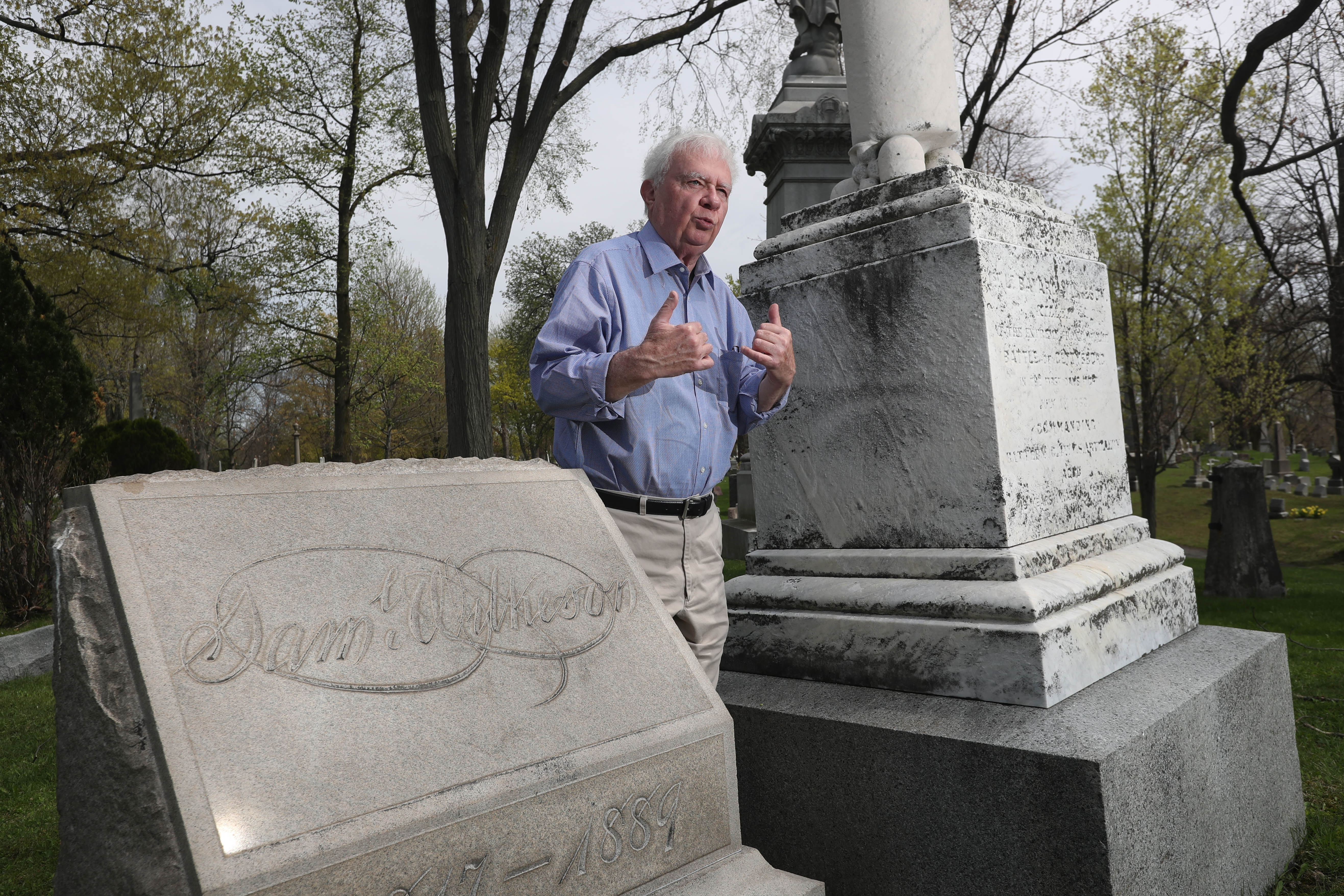 Henry Pogodzinski, who leads a summertime Civil War tour of Forest Lawn Cemetery, stands at the graves of Samuel Wilkeson Jr., left,  and his son Bayard Wilkeson. (Sharon Cantillon/Buffalo News)