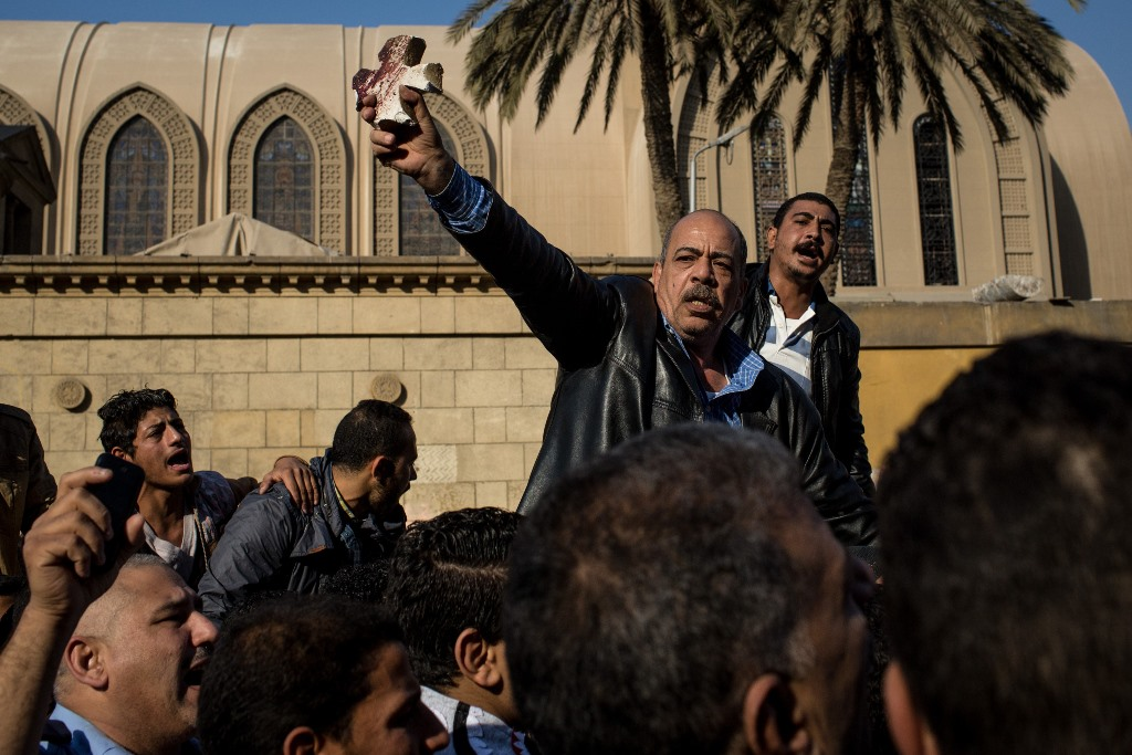A man holds up a bloodied piece of rubble in the shape of a cross as people rallied in the street outside the church of St Peter and St Paul in the Coptic Cathedral complex on December 11, 2016 in Cairo, Egypt. At least 25 people were killed and dozens injured after an explosion near the church. (Getty Images)