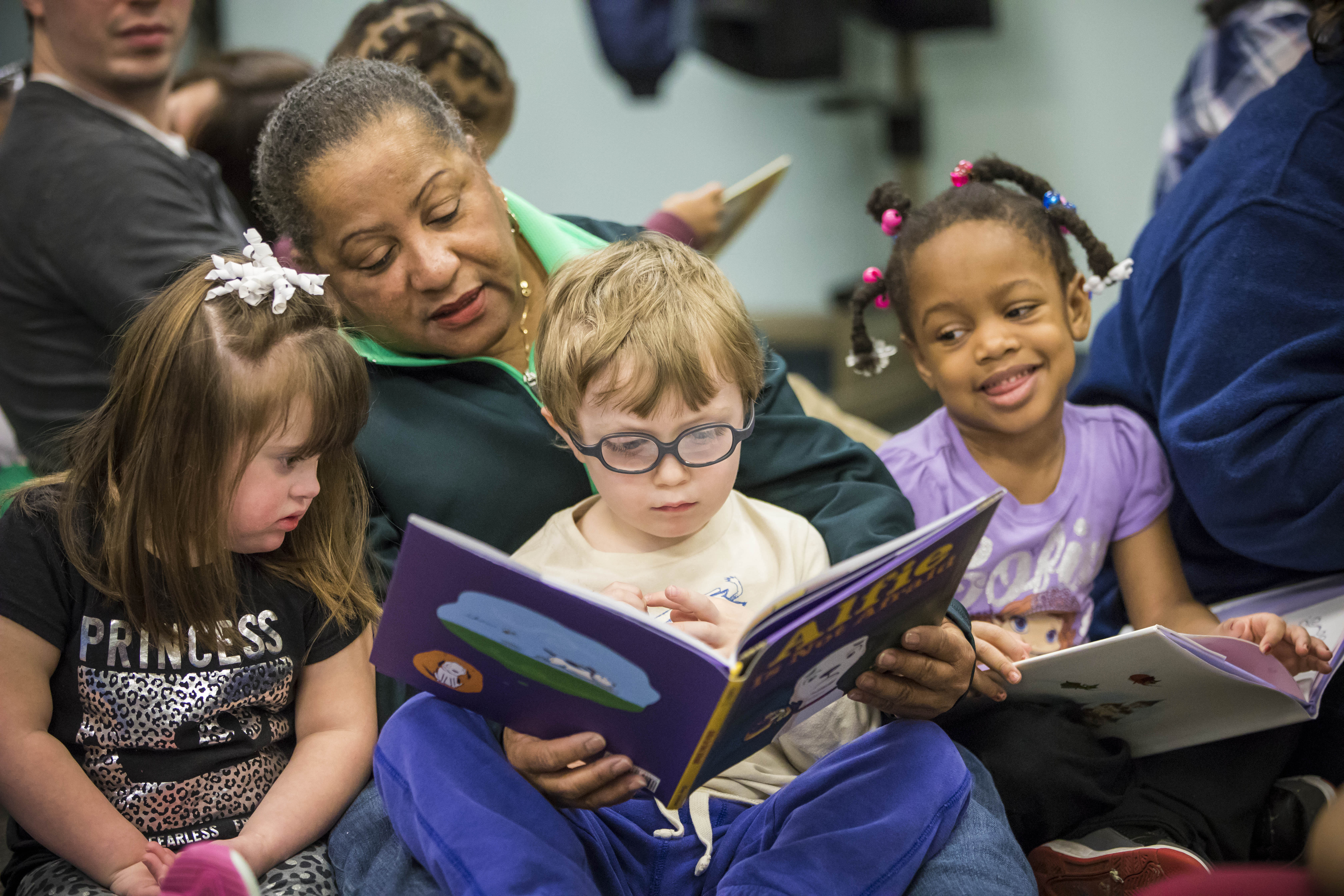 Personal aide Meota Jones reads to students, from left, Sofia Kotarski, Ethan Blair and Amil Marshall, all age 4, during the annual Books for Kids campaign kickoff at the Buffalo Hearing and Speech Center, Tuesday, April 4, 2017.  (Derek Gee/Buffalo News)