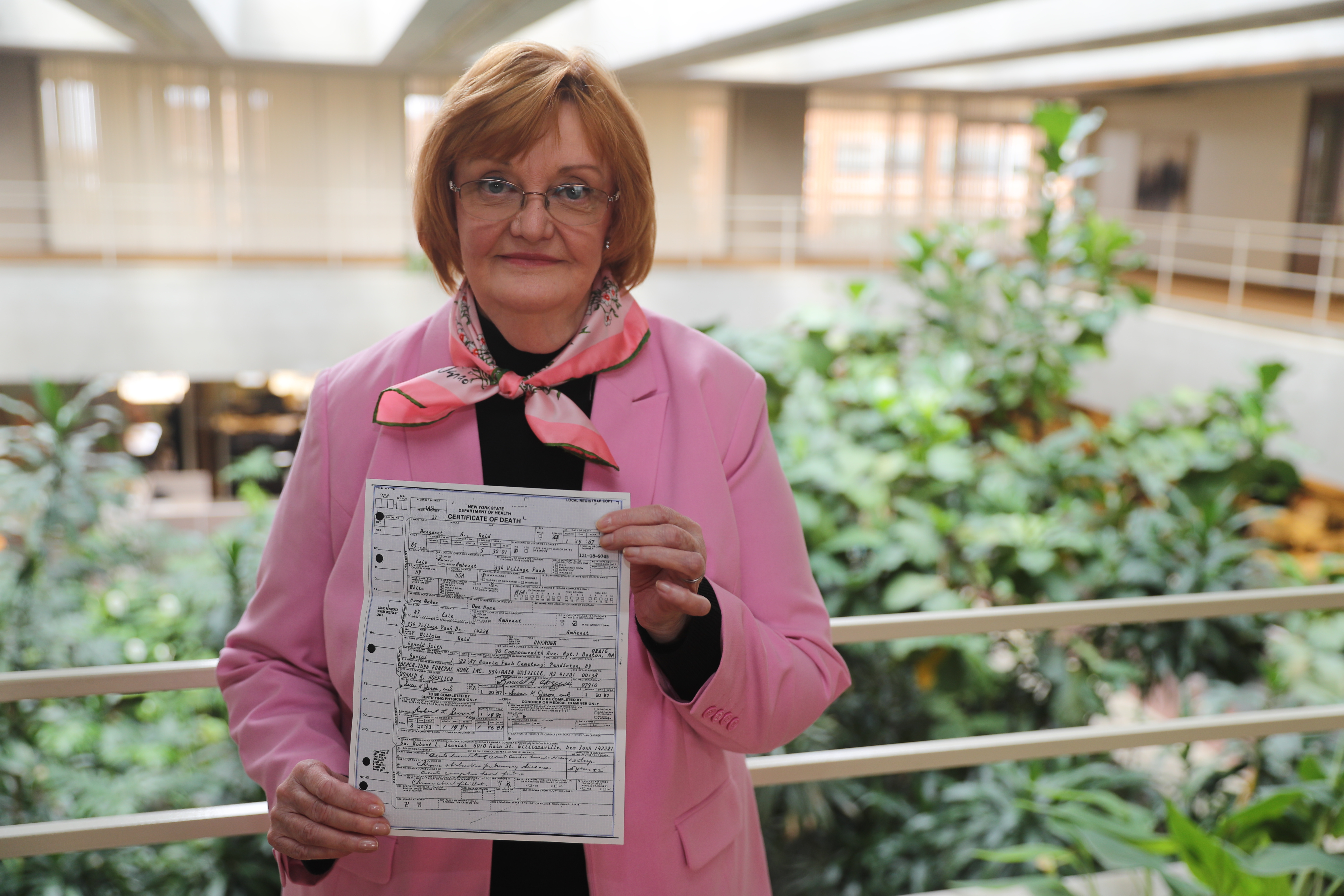 Amherst resident Lois Reid holds a copy of a death certificate for her aunt that it took her 10 months and two court decisions to obtain. (John Hickey/Buffalo News)