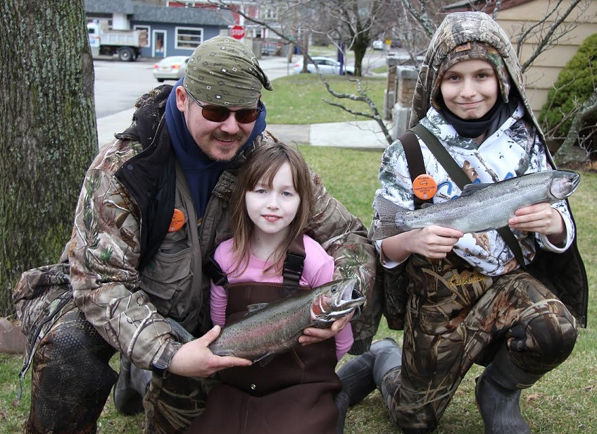 """Thomas Pustulka of Buffalo with his daughter Illyanna and nephew Camren with the fish they caught during the 56th Annual Opening Day Naples Rainbow Trout Fishing Derby. Illyanna won the """"Girls Under 16 Years Division with her 2.60- pound rainbow."""
