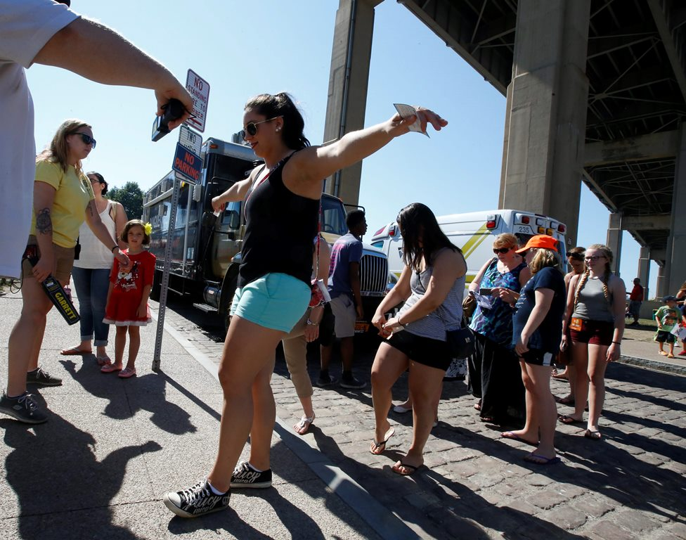 A security officer uses a wand to screen fans headed into a celebrity meet-and-greet session at the Kiss the Summer Hello concert at Canalside last June. (Harry Scull Jr./News File Photo)