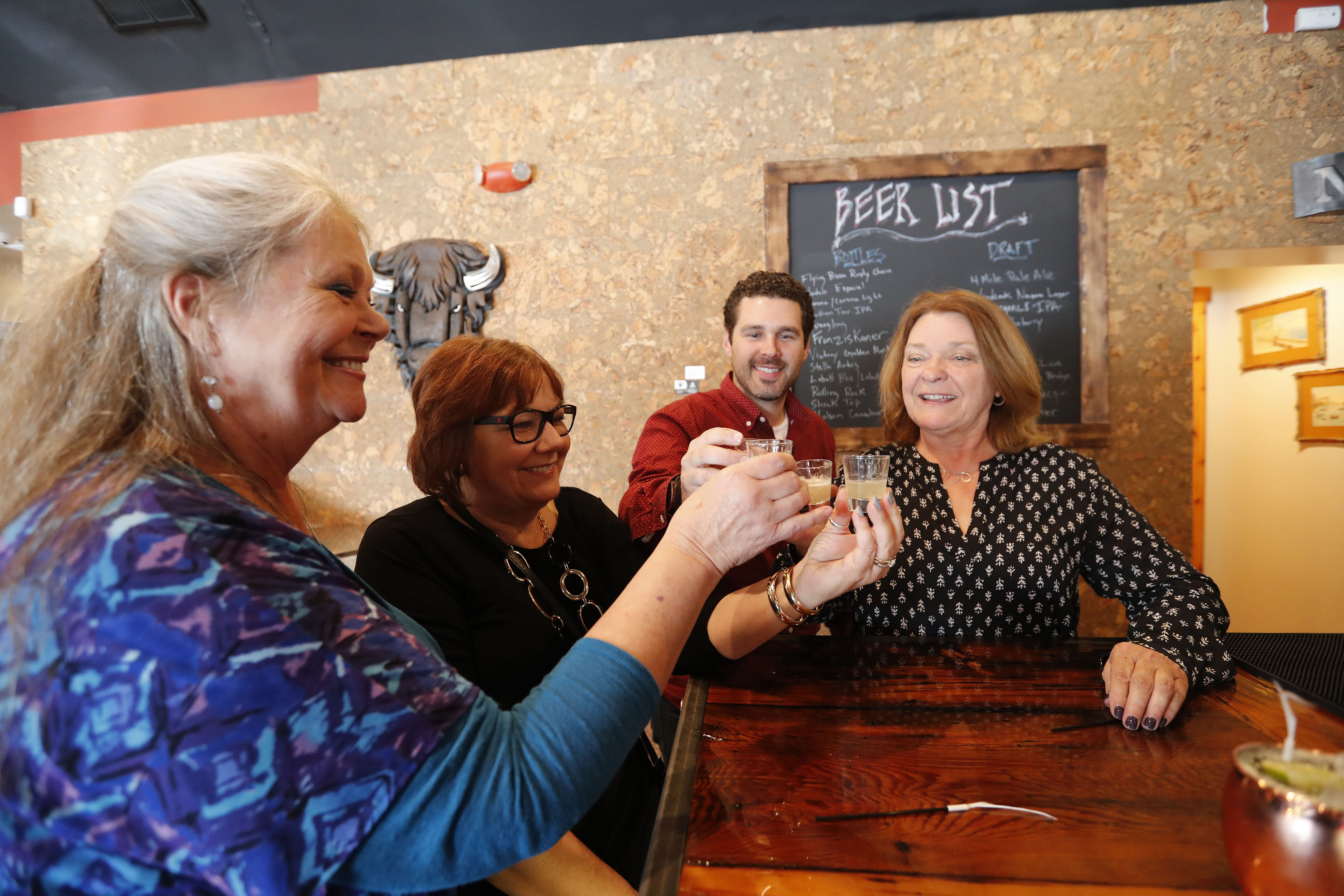 Eva Nicklas, left, Irene Rykaszewski, Michael Hibbard and Kathryn Serianni sample different versions of the new Morgan Mule at Gallo Coal Fire Kitchen. The cocktail, sampled at the spot where Catherine Hustler's tavern once stood, will be sold at A Taste of Lewiston May 27. (Mark Mulville/Buffalo News)