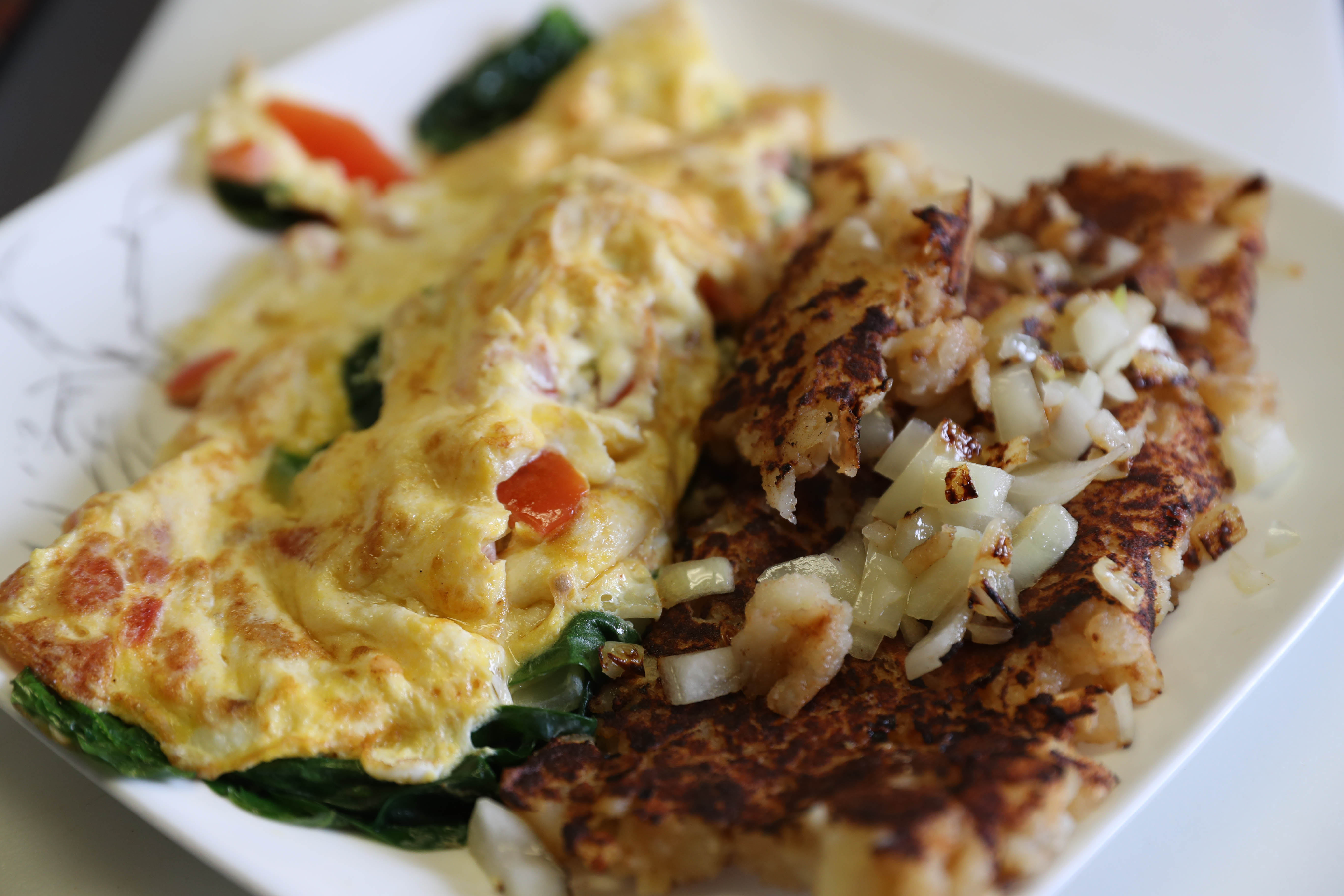 A custom omelet with tomato, onion, spinach and feta with home fries and onions at Rooser's Cafe.  (Sharon Cantillon/Buffalo News)