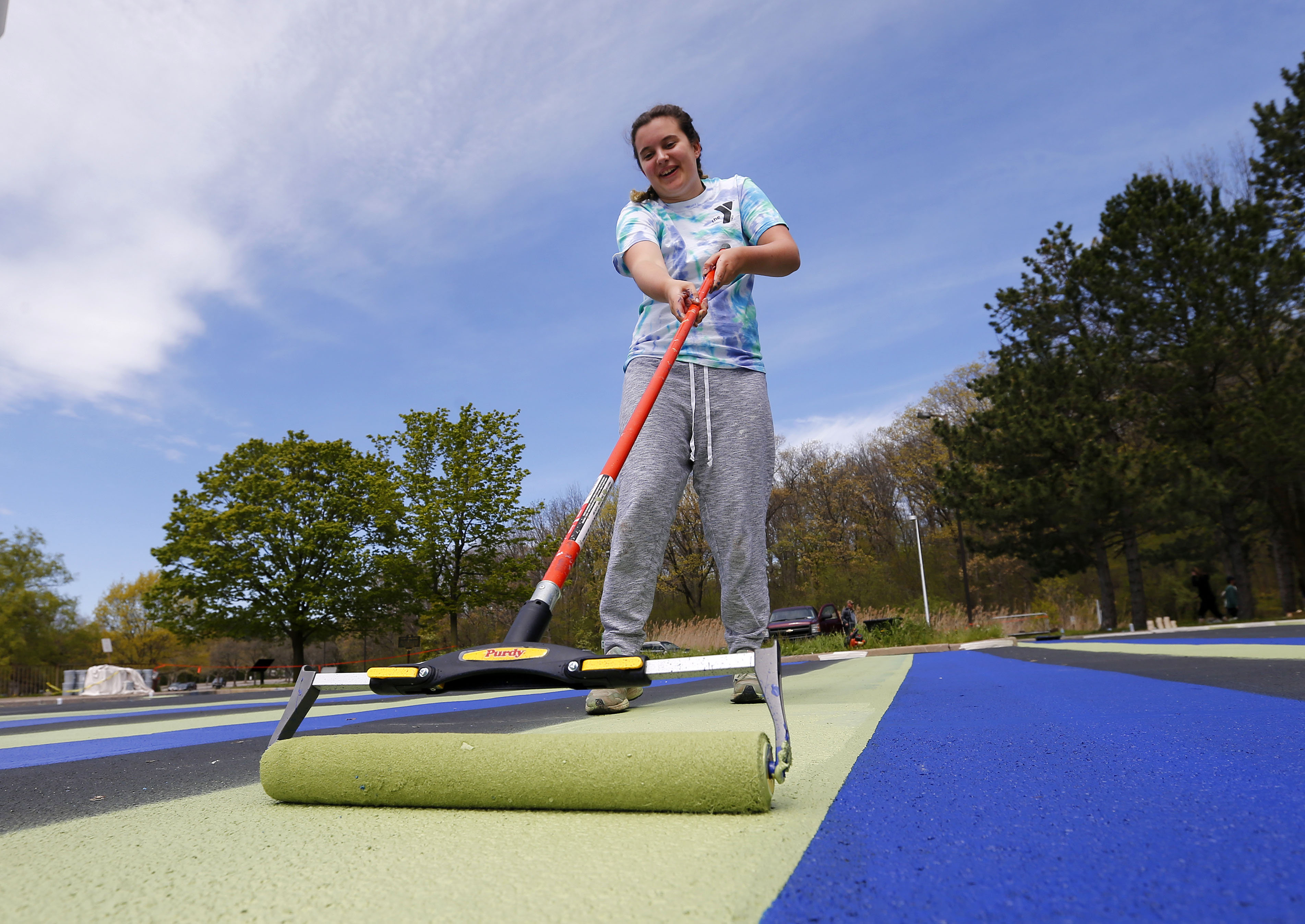 Lewiston-Porter High School art student Bailey Hoplight helps recreate the painted parking lot at Artpark State Park in Lewiston. (Mark Mulville/Buffalo News)