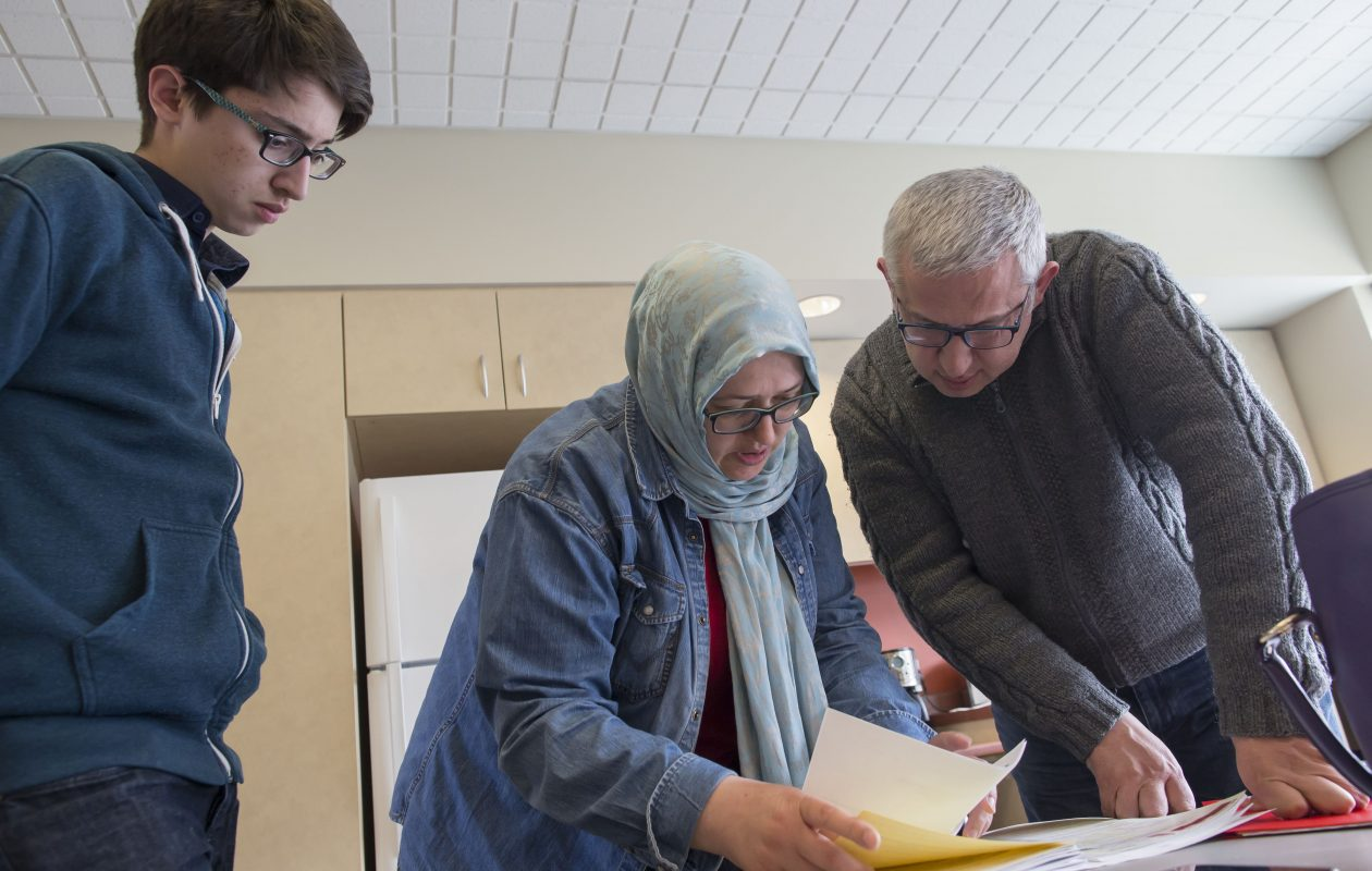 Turkish immigrant Incilay Kircali, center, and her husband, Hakan, review Incilay's application for asylum in Canada at the Peace Bridge Newcomer Centre in Fort Erie, Ont. (Derek Gee/Buffalo News)
