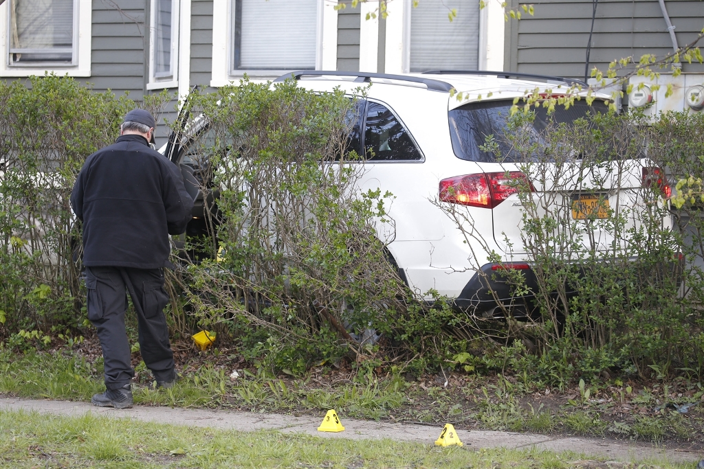 A Buffalo police officer at the scene where Jose Hernandez-Rossy's SUV crashed into a house.  The blood of Officer Joseph Acquino was found on the deployed airbag in the vehicle. (Robert Kirkham/Buffalo News)