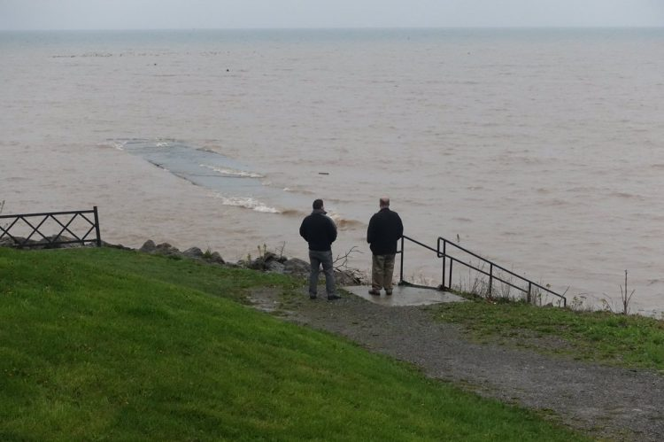 Doug Hoopsock, left,  and Josh Kanouse look at Lake Ontario as the rising water washes over the old Wilson Pier. (John Hickey/Buffalo News)