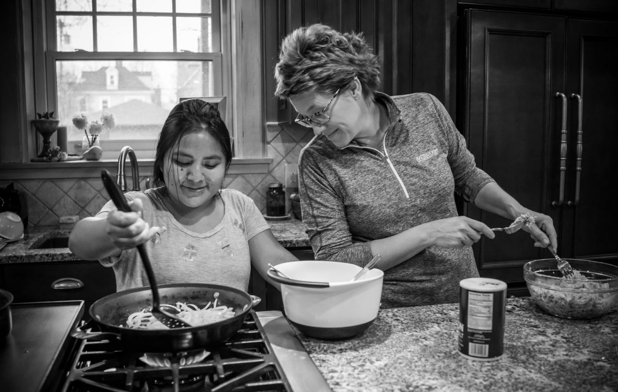 Sandra, an immigrant from Guatamala without legal status in the U.S., prepares dinner with Joelle Herskind in the Herskind's kitchen. While living together, Sandra and Joelle Herskind traded recipes, with Sandra teaching Joelle how to make guacamole and salsa and Joelle teaching Sandra how to make chocolate chip cookies and apple pie. (Derek Gee/Buffalo News)