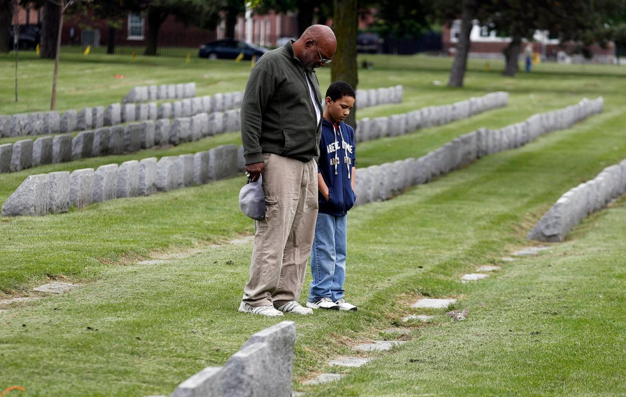 Grover Coleman Jr. and his grandson, Aidan, at the Forest Lawn Cemetery gravesite of Grover's father. (John Hickey/Buffalo News)